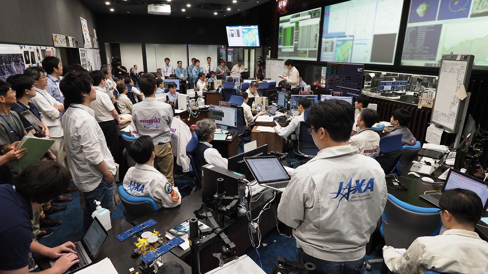 Investigadores y empleados, realizando una sesión informativa en la sala de control de la misión Hayabusa 2 en la ciudad de Sagamihara (Foto de Yutaka IIJIMA / ISAS-JAXA / AFP)
