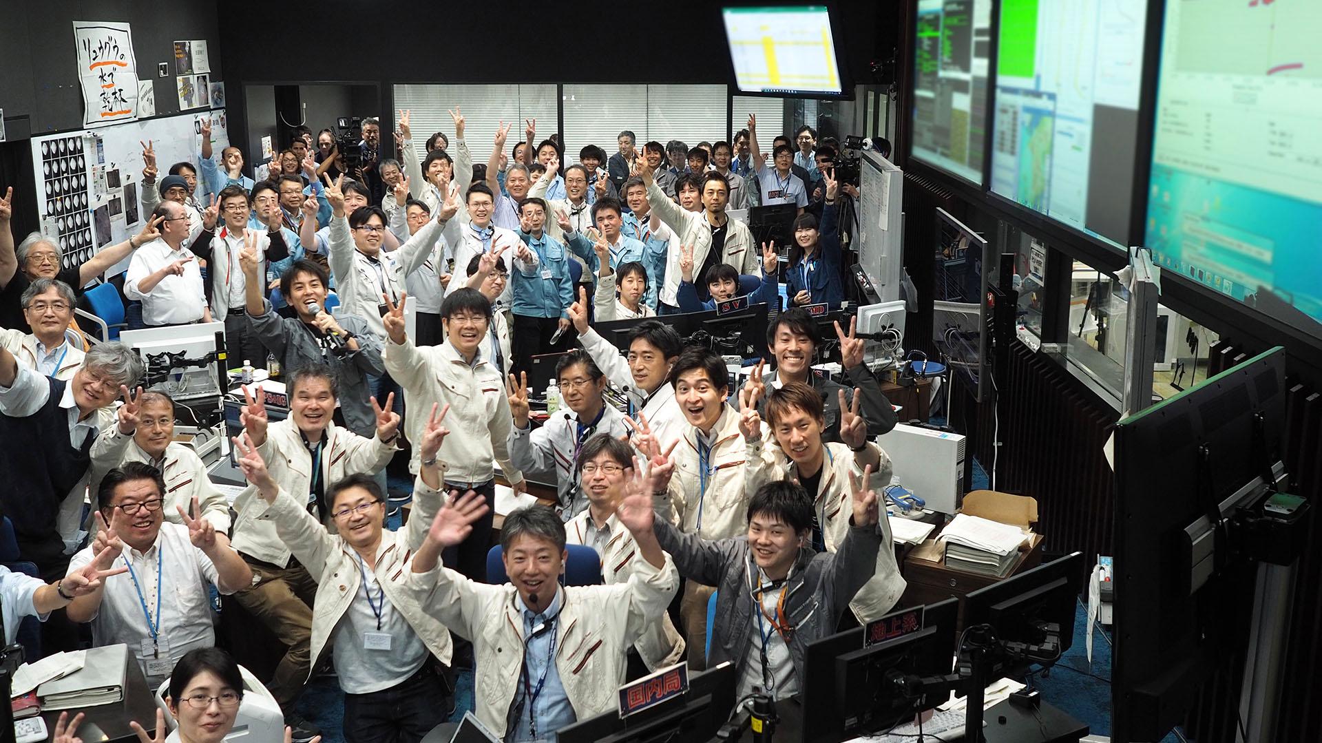 Esta fotografía del 11 de julio muestra a investigadores y empleados celebrando después de recibir la confirmación del aterrizaje de Hayabusa 2 en el asteroide Ryugu, en la sala de control de la misión en la ciudad de Sagamihara, prefectura de Kanagawa (Foto de Yutaka IIJIMA / ISAS-JAXA / AFP)