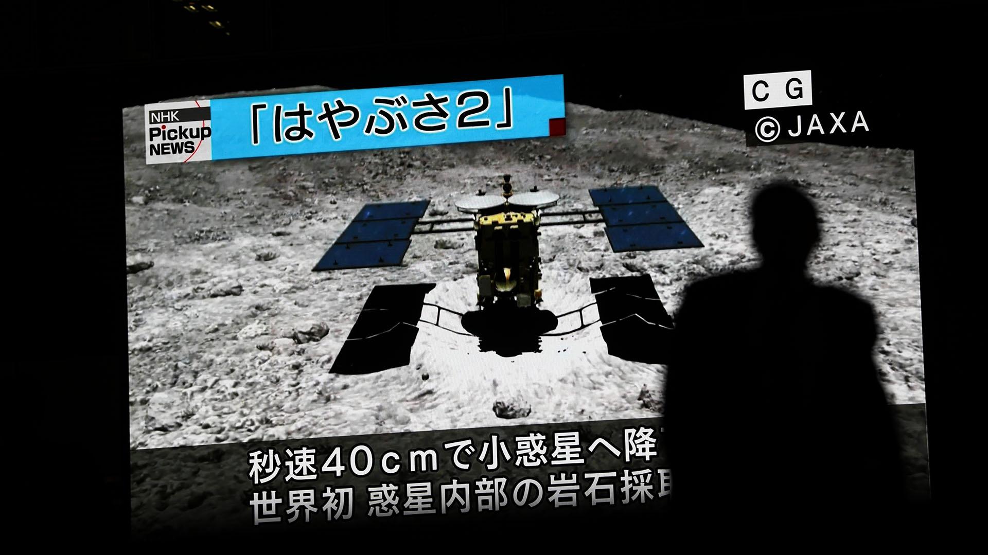 En esta foto tomada el 10 de julio de 2019, un hombre pasa junto a una pantalla que muestra una imagen generada por ordenador de la sonda Hayabusa 2, durante un noticiero emitido en el distrito de Akihabara en Tokio (Foto de Behrouz MEHRI / AFP)
