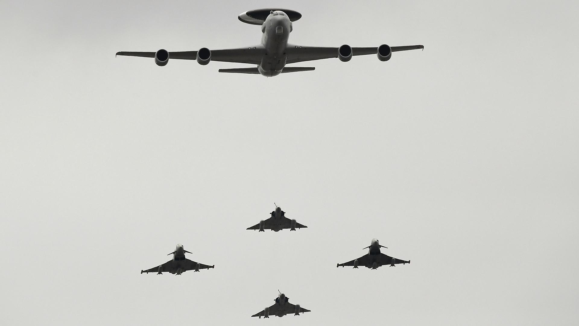 Aviones militares sobre París: Boeing E-3 Sentry (arriba), Mirage 2000 (vertical, rombo) y Eurofighter Typhoon (izquierda y derecha)