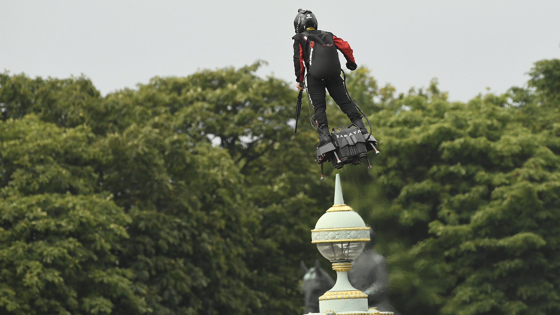 """Un hombre volando en un """"flyboard"""" en los Campos Elíseos"""