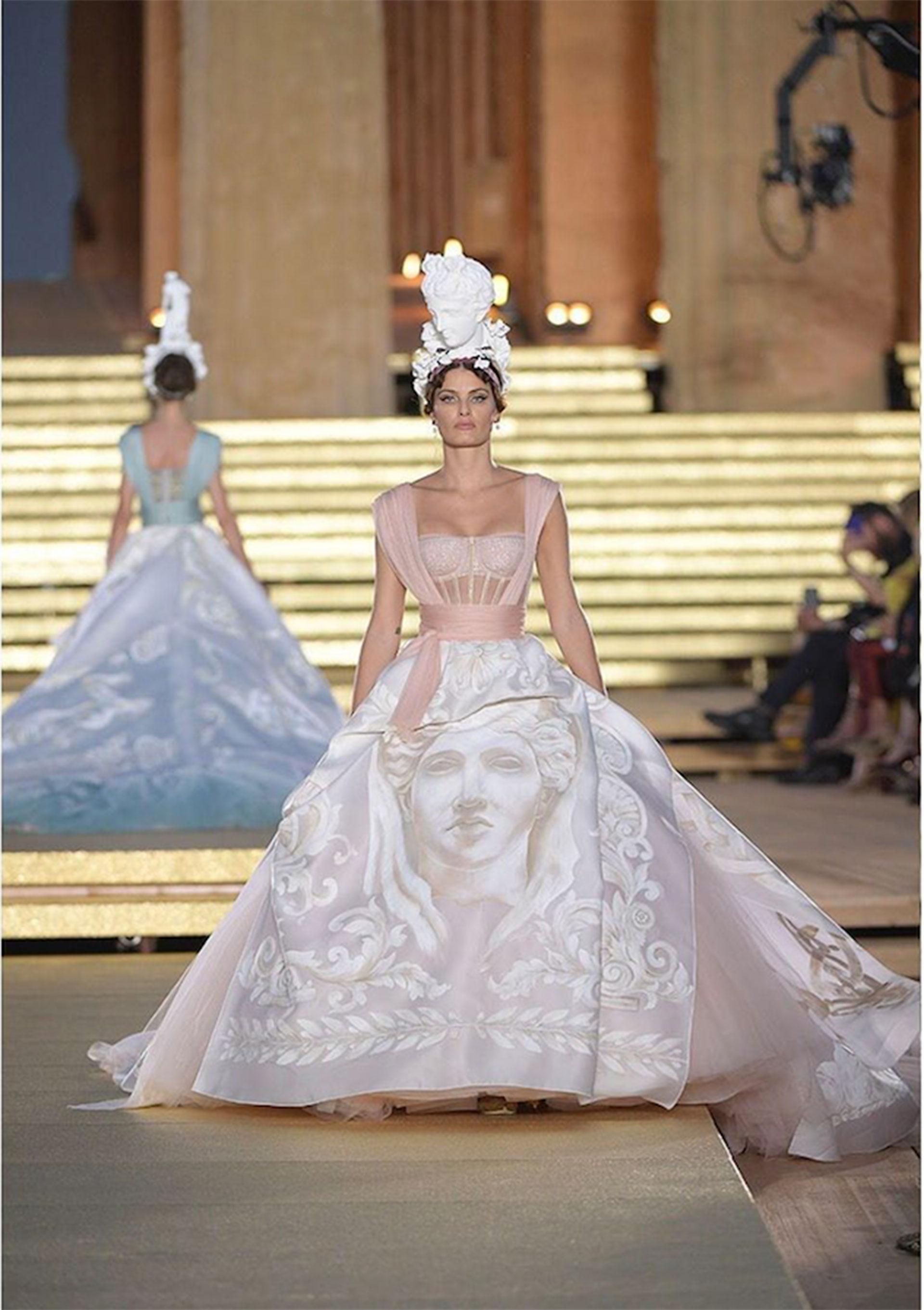 La top model brasilera Isabeli Fontanallevaun vestido con corsé de tul ilusionado. La falda drapeada de organza doble está pintada a mano y cuenta las obras y cualidades de Hera.