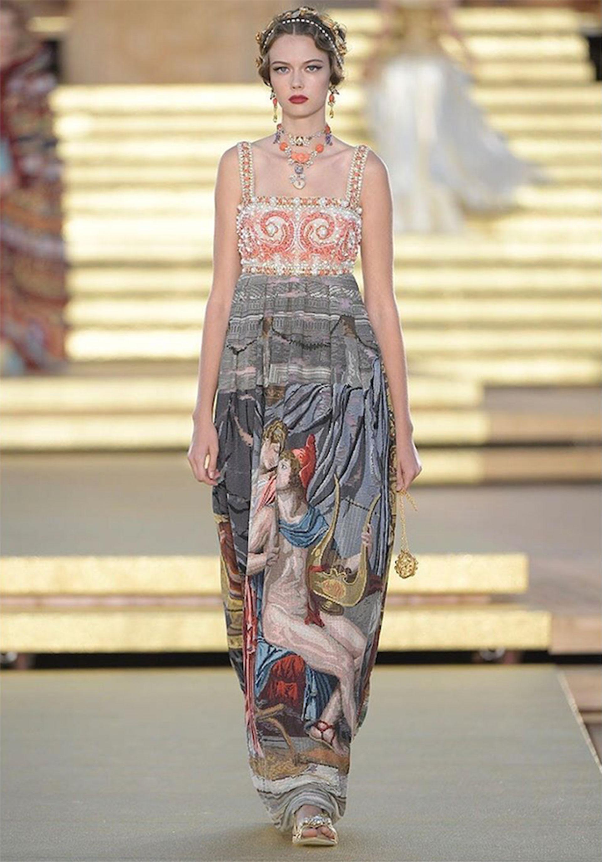 Vestido de la línea Imperial con top corset bordado con cristales de lentejuelas y corales reales. La falda está totalmente bordada con la técnica de punto de cruz, reproduciendo la obra de Jacques Luois David, el amor de Helen y Pericles, 1789.