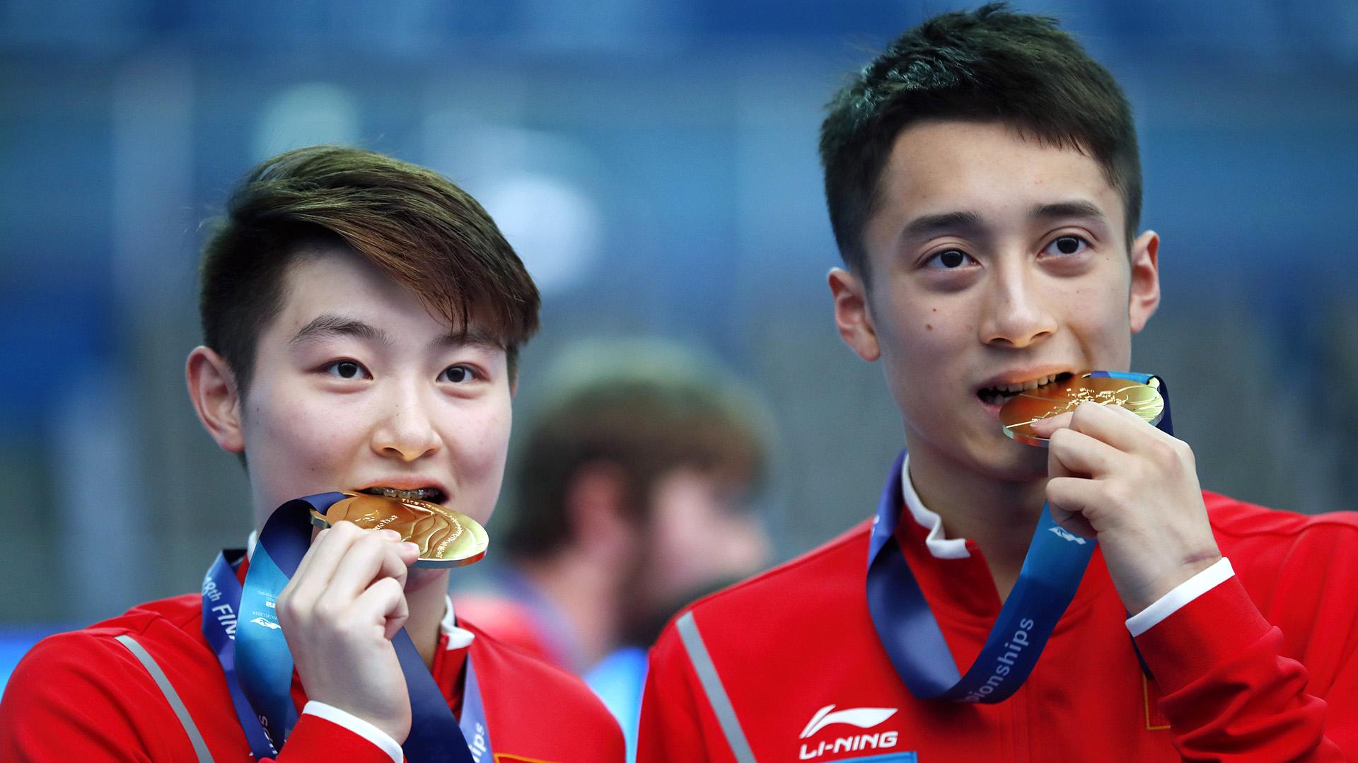 """Los chinos Si Yajie y Lian Junjie """"prueban"""" sus medallas de oro"""