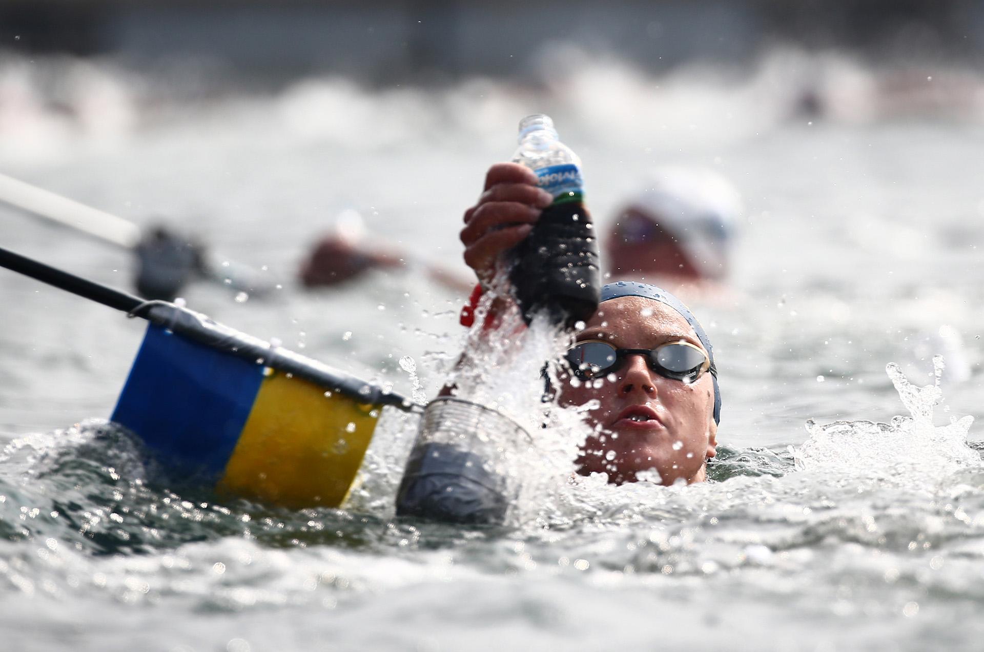 La ucraniana Krystyna Panchishkorecibe algo para hidratarse durante la final de los 10 kilómetros en aguas abiertas