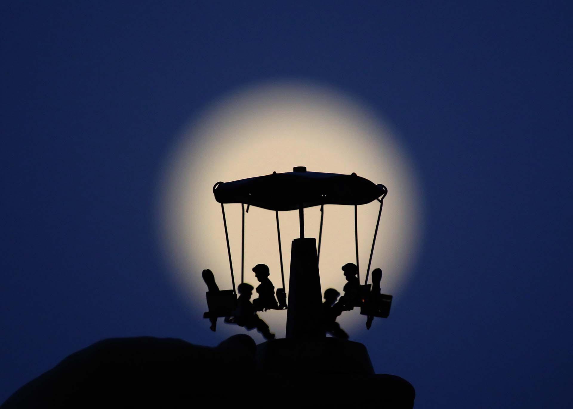Una luna llena frente a un carrusel en Nicosia, Chipre(EFE/EPA/KATIA CHRISTODOULOU)