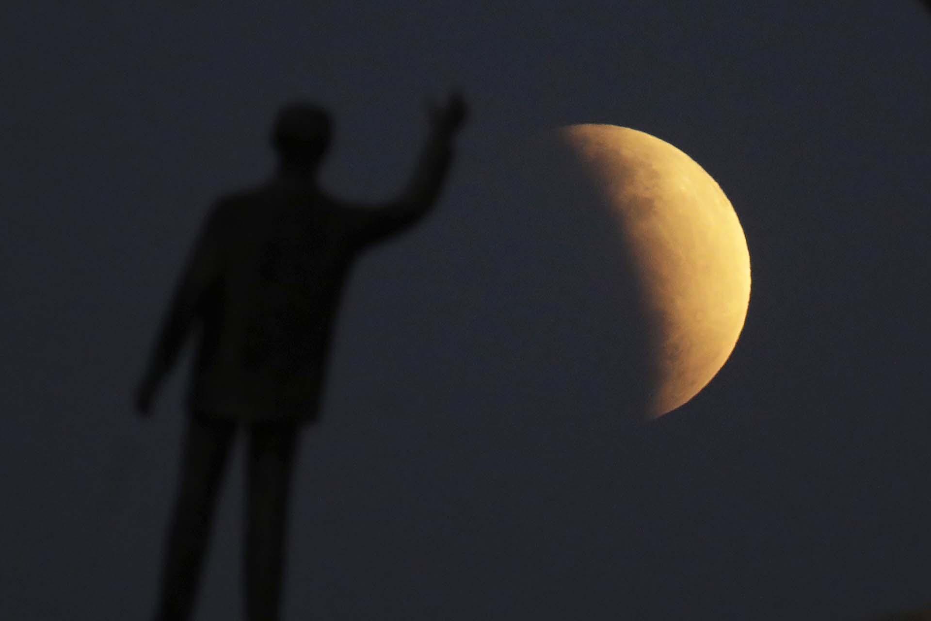 Una estatua del ex presidente brasileño Juscelino Kubitschekfrenteal eclipse lunar parcial enel cielo de Brasilia el martes 16 de julio de 2019. El fenómeno visto en todo Brasil llegó el mismo día que el 50º aniversario de los alunizajes (AP Photo/Eraldo Peres)
