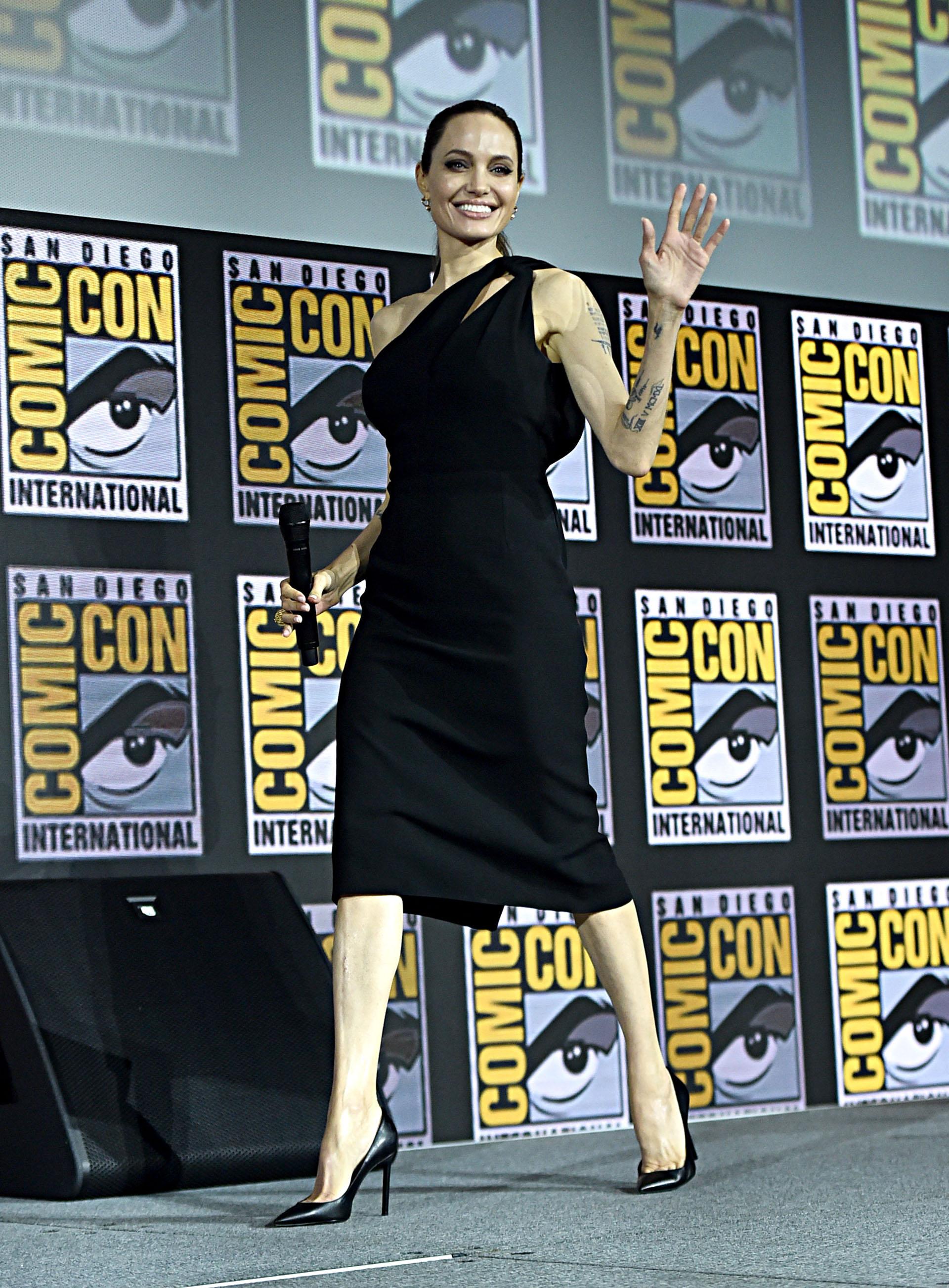 Como nueva superheroína de Marvel en la película The Eternals -Angelina Jolie – eligió un total black look para el panel de Comic Con. Llevó un vestido midi en color negro y con escote drapeado con cut-out y stilettos negros.