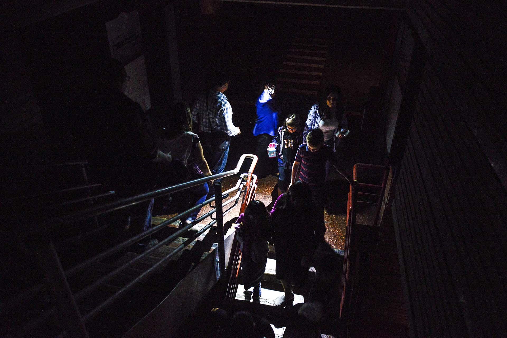 A las 4:45 PM, un corte masivo de energía eléctrica dejó a Caracas en penumbras. En un shopping del centroen Caracas, ciudadanos evacúan el edificio iluminados por la luz de un celular