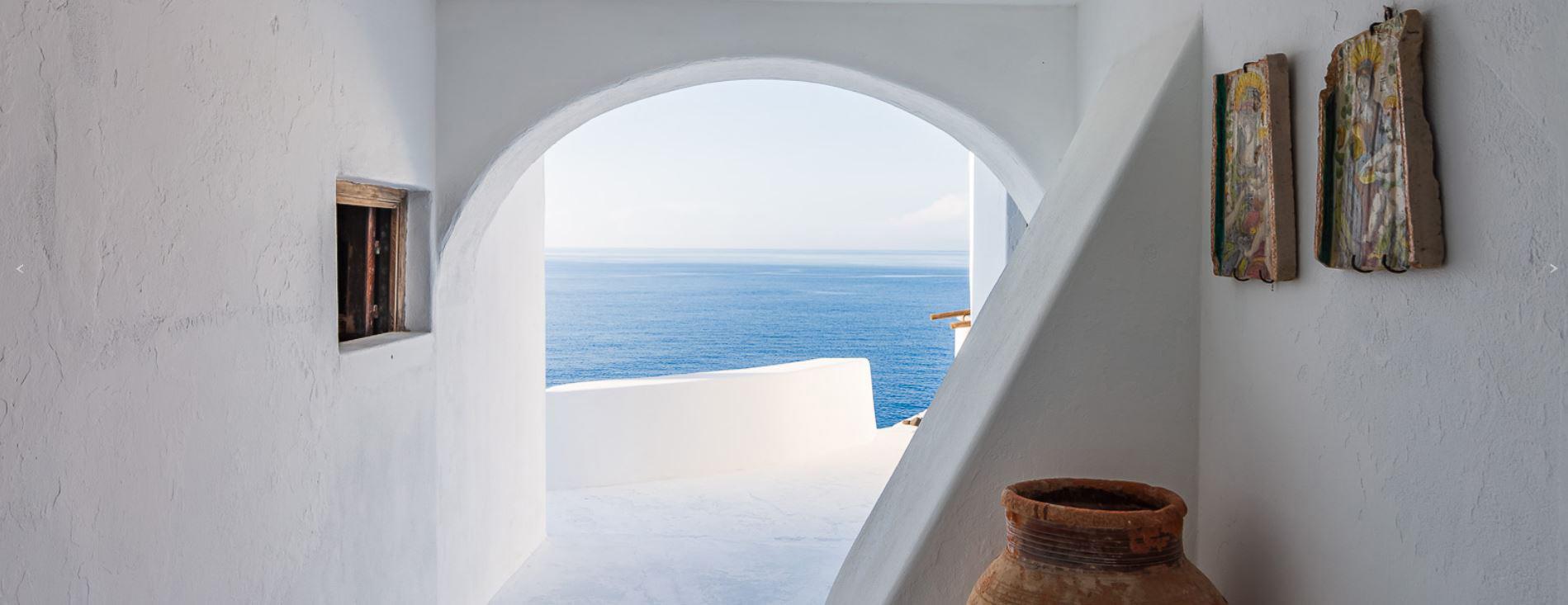 Las casas blancas ubicadas a lo largo de la costa, contrastan con la vegetación verde y el mar azul profundo