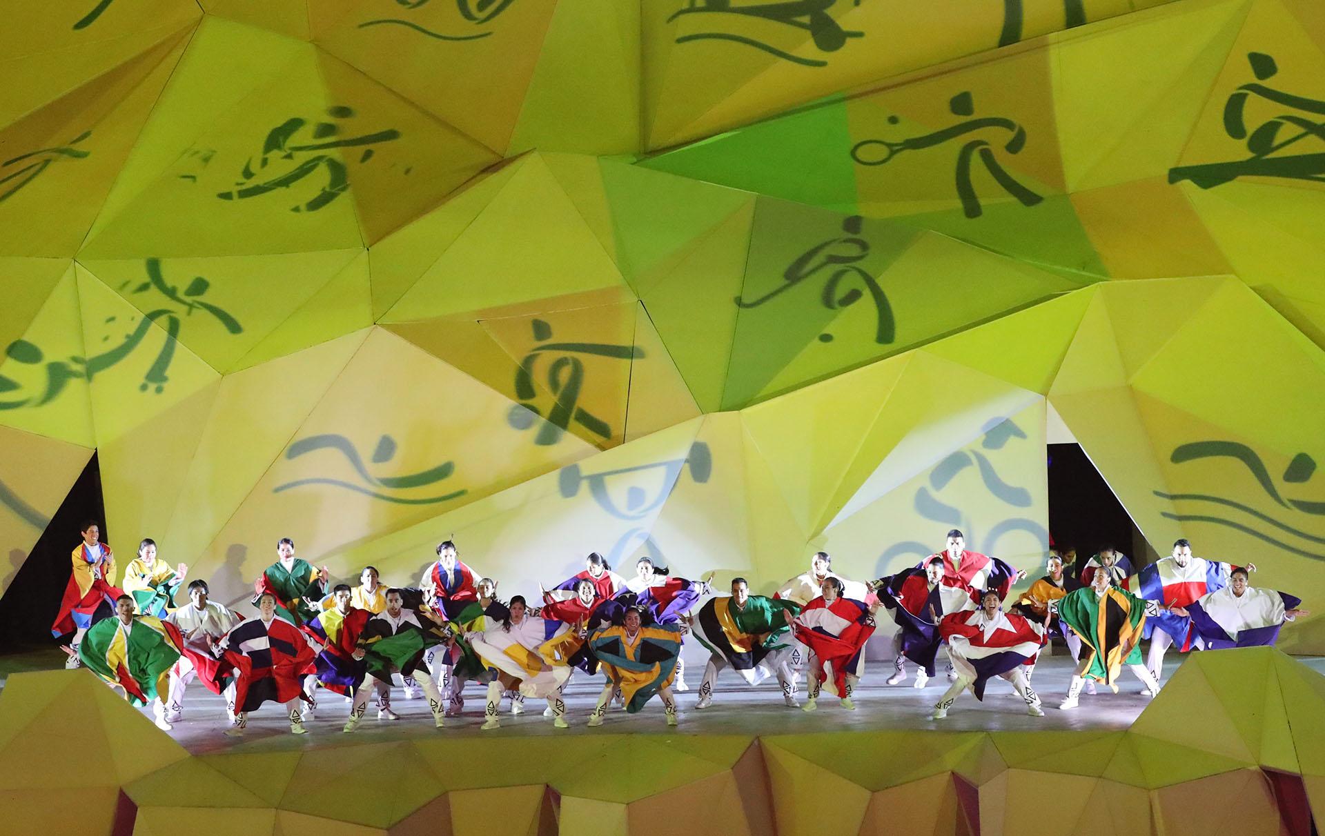 Bailarines con las banderas de los países protagonistas de los Juegos Panamericanos con los pictogramas de fondo(REUTERS/Sergio Moraes)