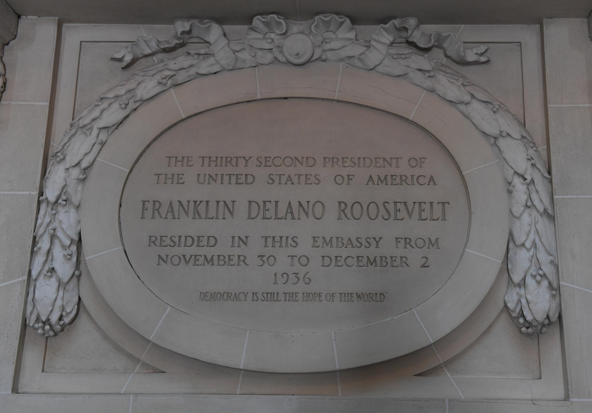 """La placa, ubicada al final de la primera parte de la escalera, da la bienvenida a los visitantes . """"El 32° presidente de los Estados Unidos de América, Franklin Delano Roosevelt, vivió en la embajada desde el 30 de noviembre hasta el 2 de diciembre de 1936. La democracia es la esperanza del mundo"""", dice la leyenda escrita sobre piedra París"""