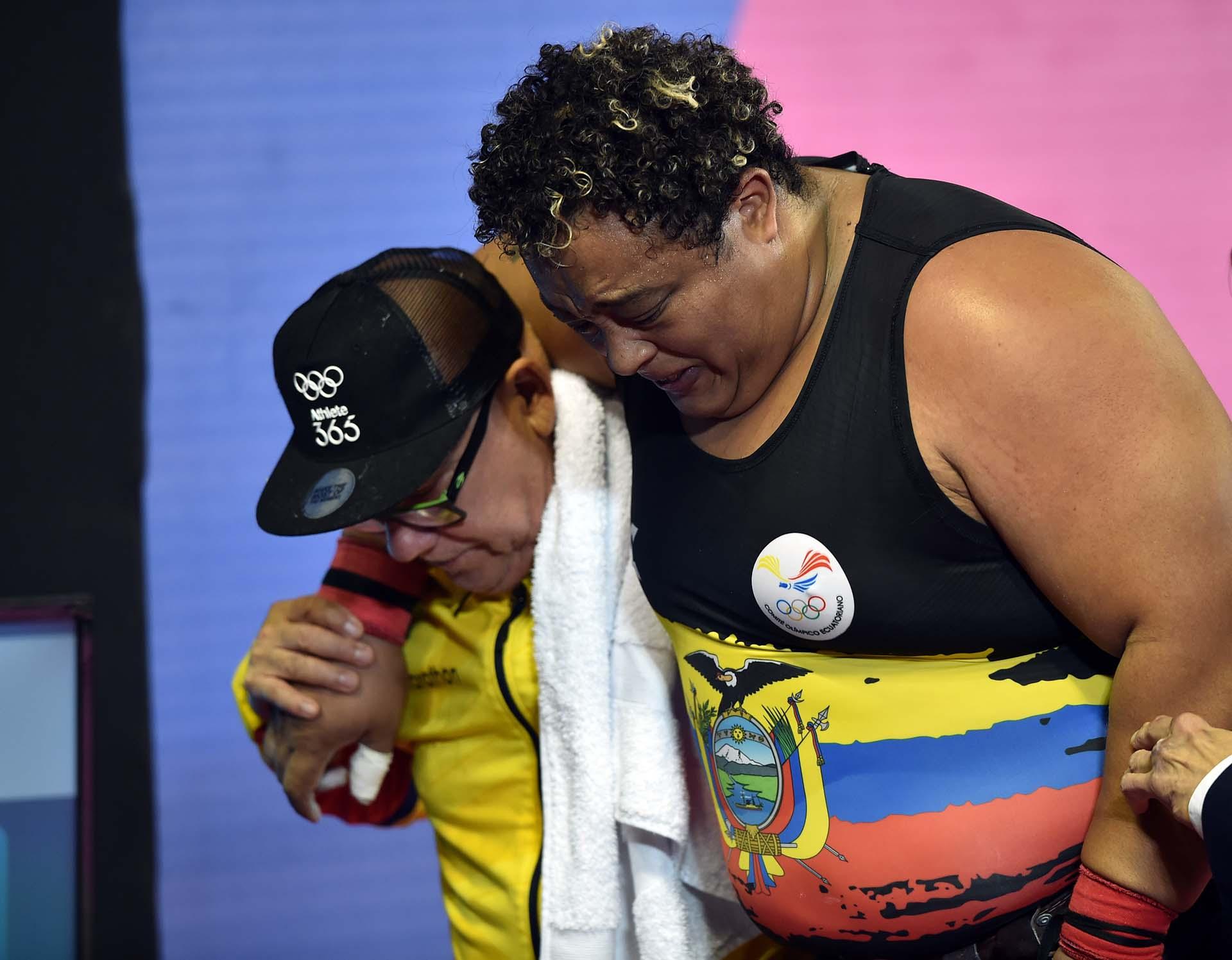 El dolor del pesista ecuatorianoFernando Salas (R) tras lesionarse en competición. (Photo by Cris BOURONCLE / AFP)