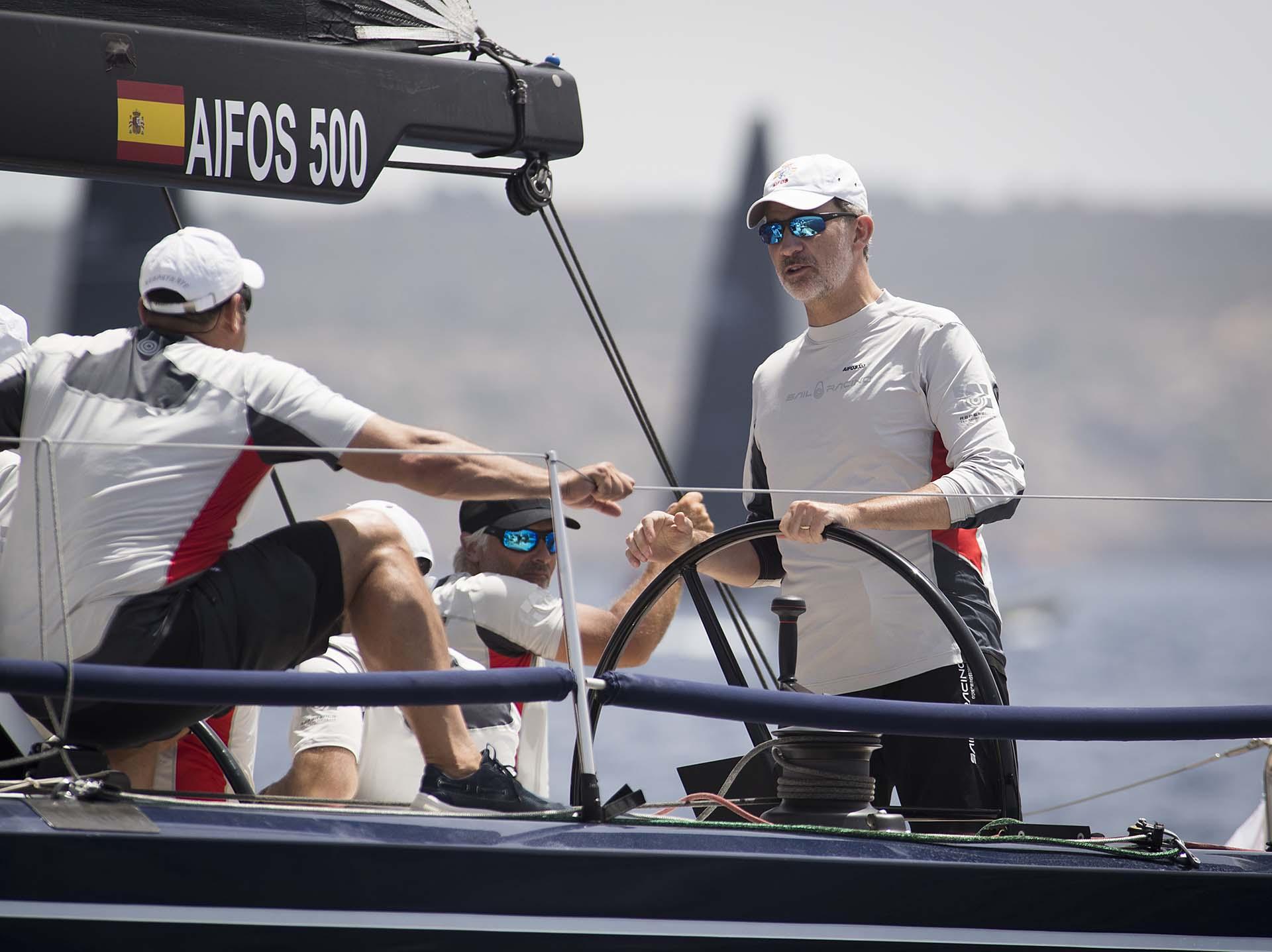 El rey españolse pone al mandodel timón del 'Aifos' el barco de la Armada Española para participar en la 38º Copa del Rey MAPFRE de Vela
