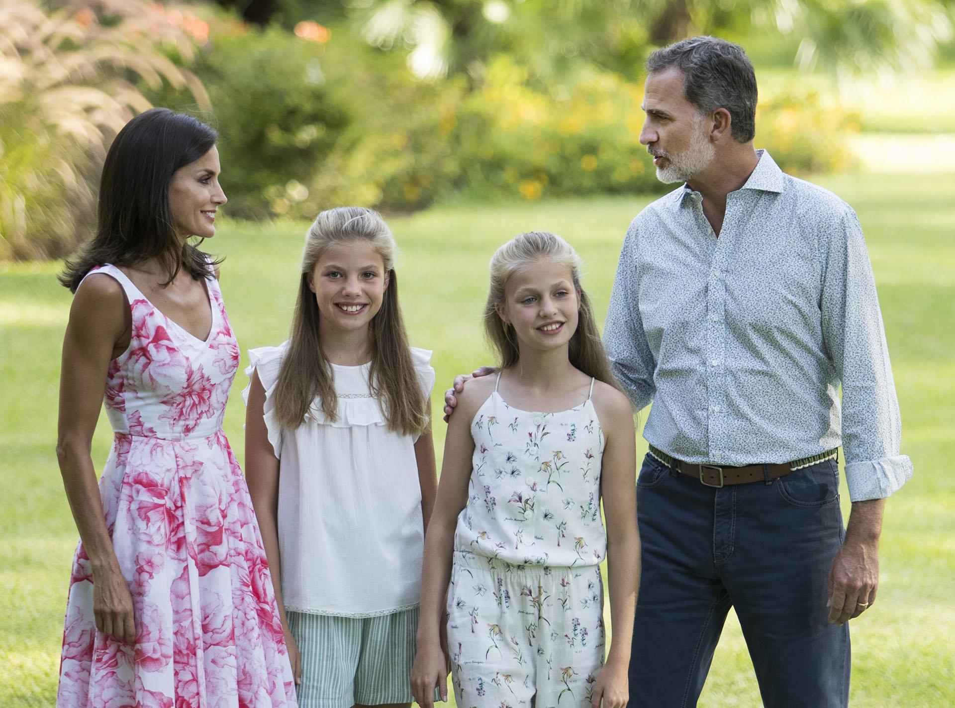 Postal completa, la reina Letizia, el rey Felipe y sus hijas, Leonor y Sofía en los jardínes del Palacio Marivent