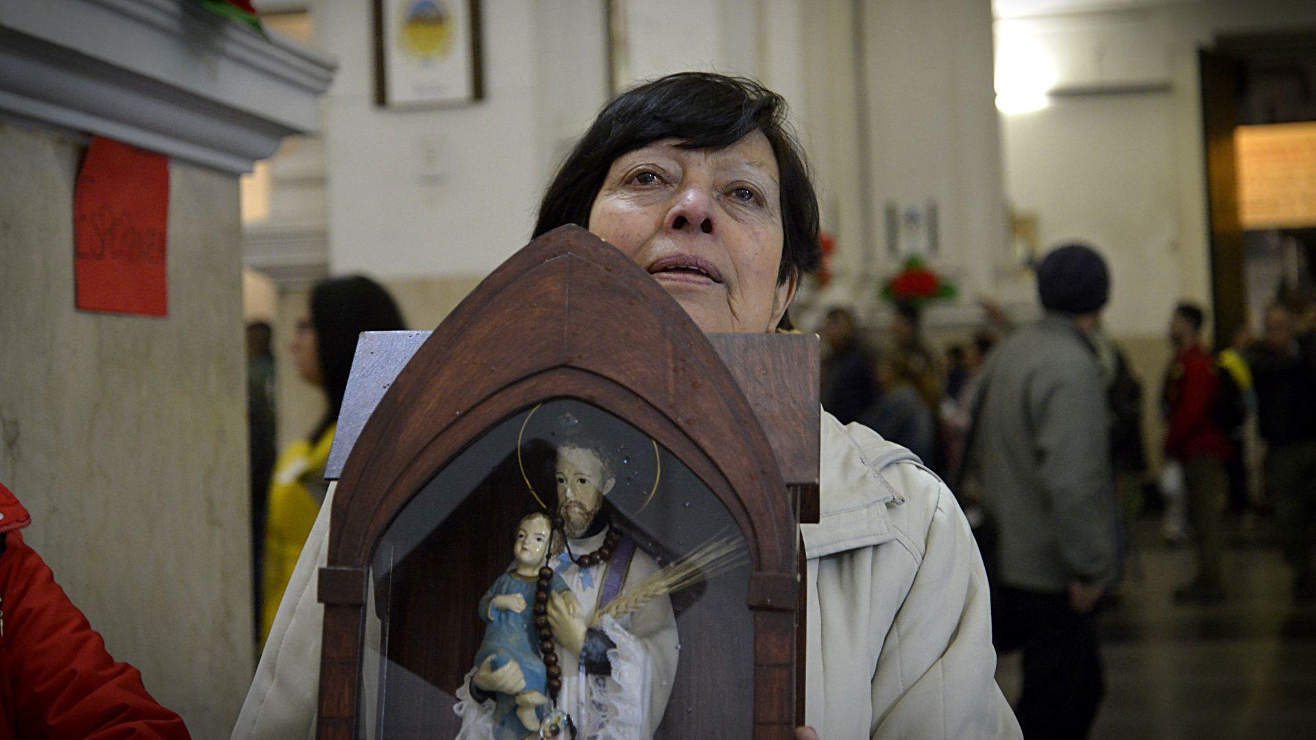 Una mujer ingresa al santuario con una figura del patrono del trabajo, un ritual que se repite año tras año entre muchos de los feligreses