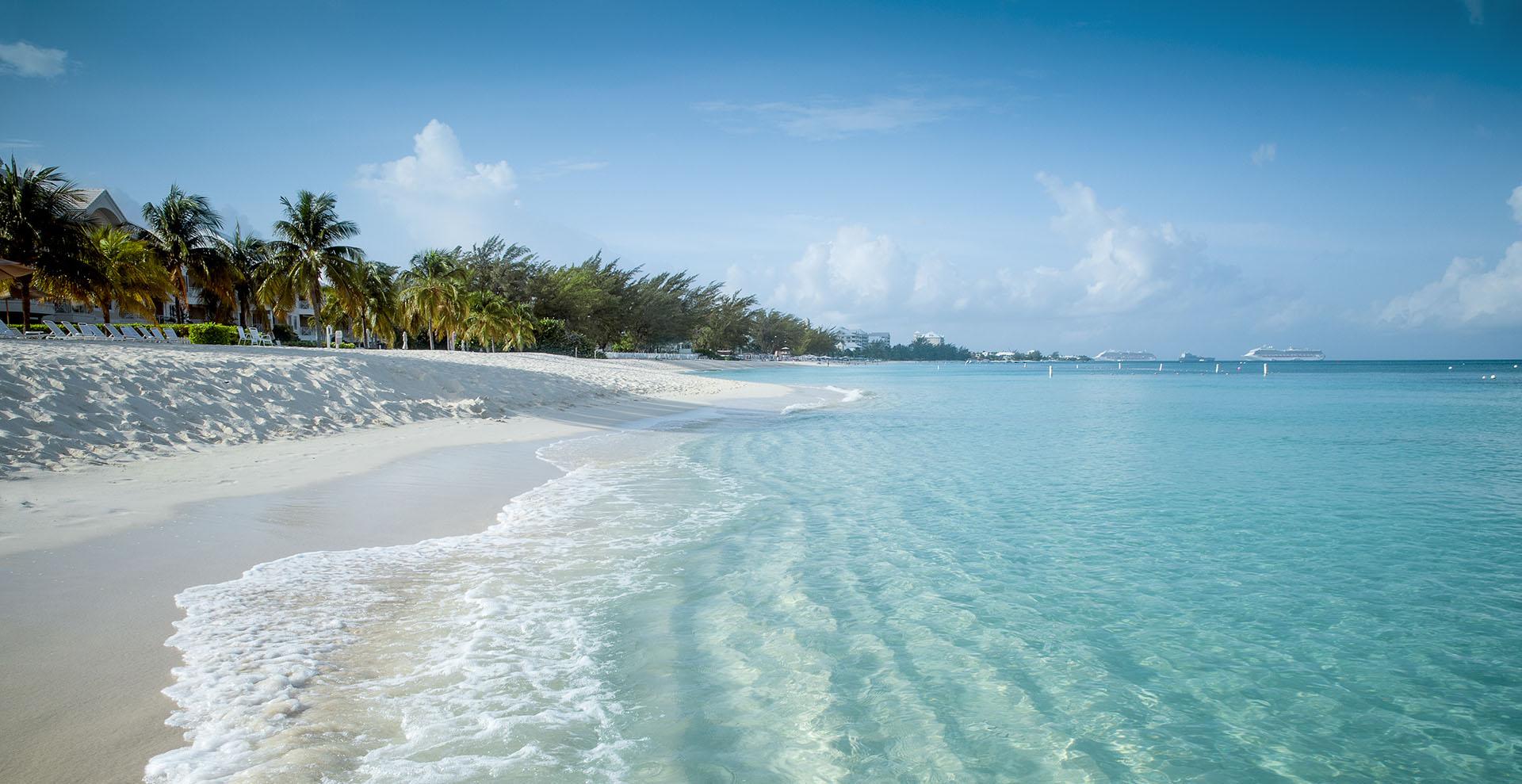 Seven Mile Beach es una de las playas más famosas del mundo. Con aguas cristalinas y arenas coralinas que se extienden a lo largo de 5,5 millas