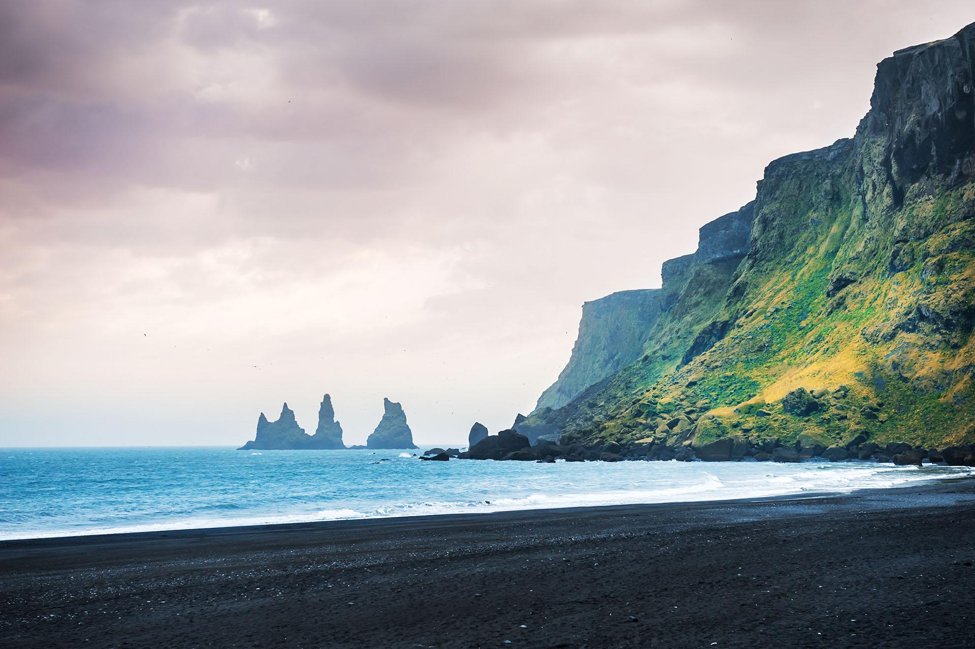 Opuesto a las playas tropicales, esta hermosa playa de arena negra en Islandia es única en el mundo, con enormes pilas de basalto que se levantan del mar y arena negra inusual