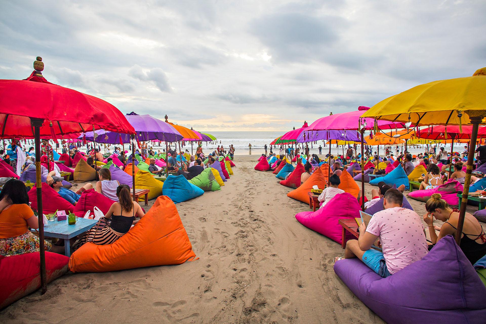 En Bali, la playa de Seminyak tiene una costa espléndida de arena oscura y hermosas puestas de sol, con un ambiente animado y muchos bares de playa caracterizados por sus sillones en la arena