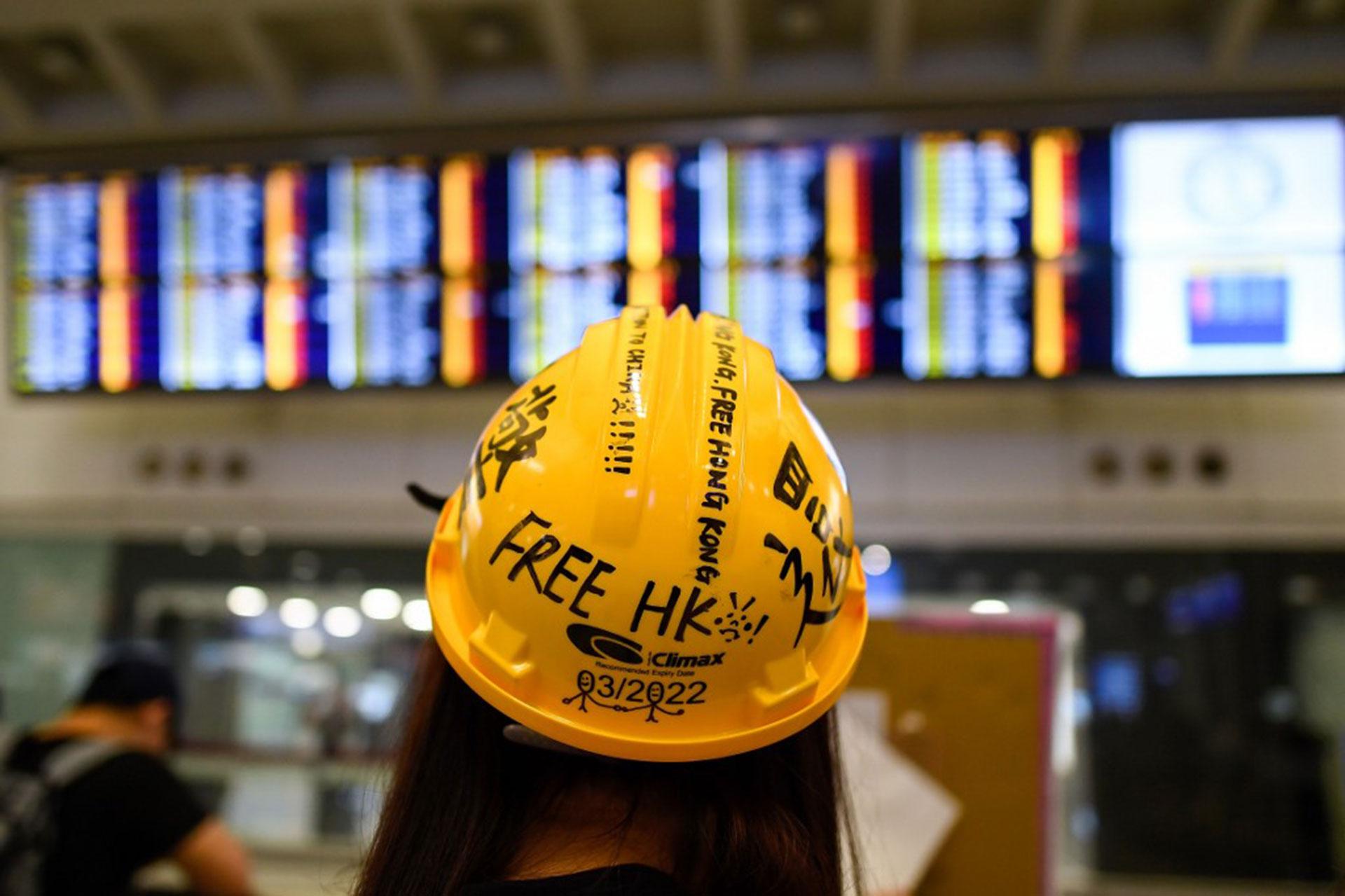 Unajovenobserva el tablero de anuncios de vuelos cancelados durante la protesta contra la brutalidad policial y el controvertido proyecto de ley de extradición en Hong Kong (Foto de Manan VATSYAYANA / AFP)