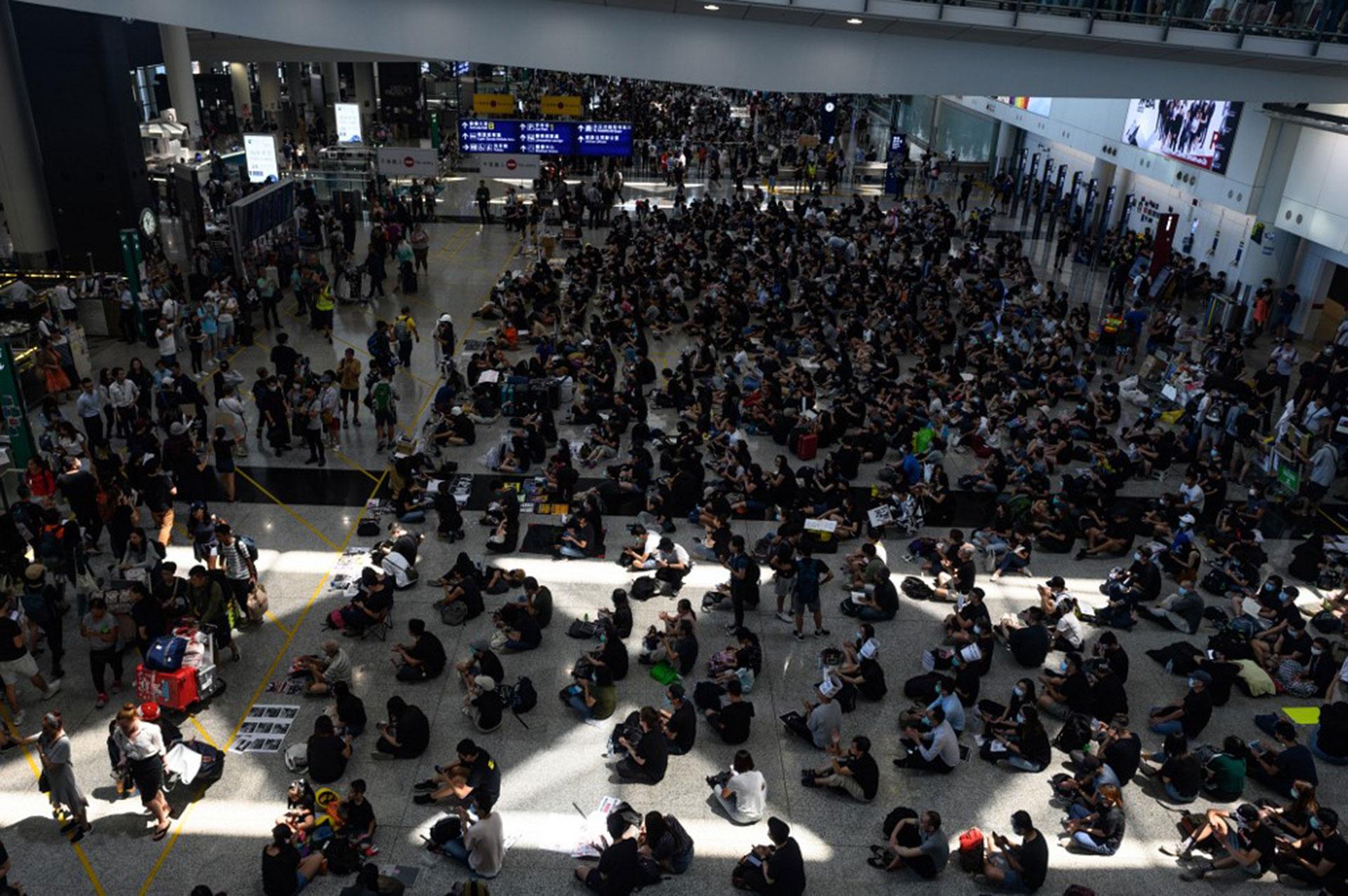 Cientos de manifestantes a favor de la democracia, en un un nuevo mitin en el aeropuerto de Hong Kong (Foto de Philip FONG / AFP)