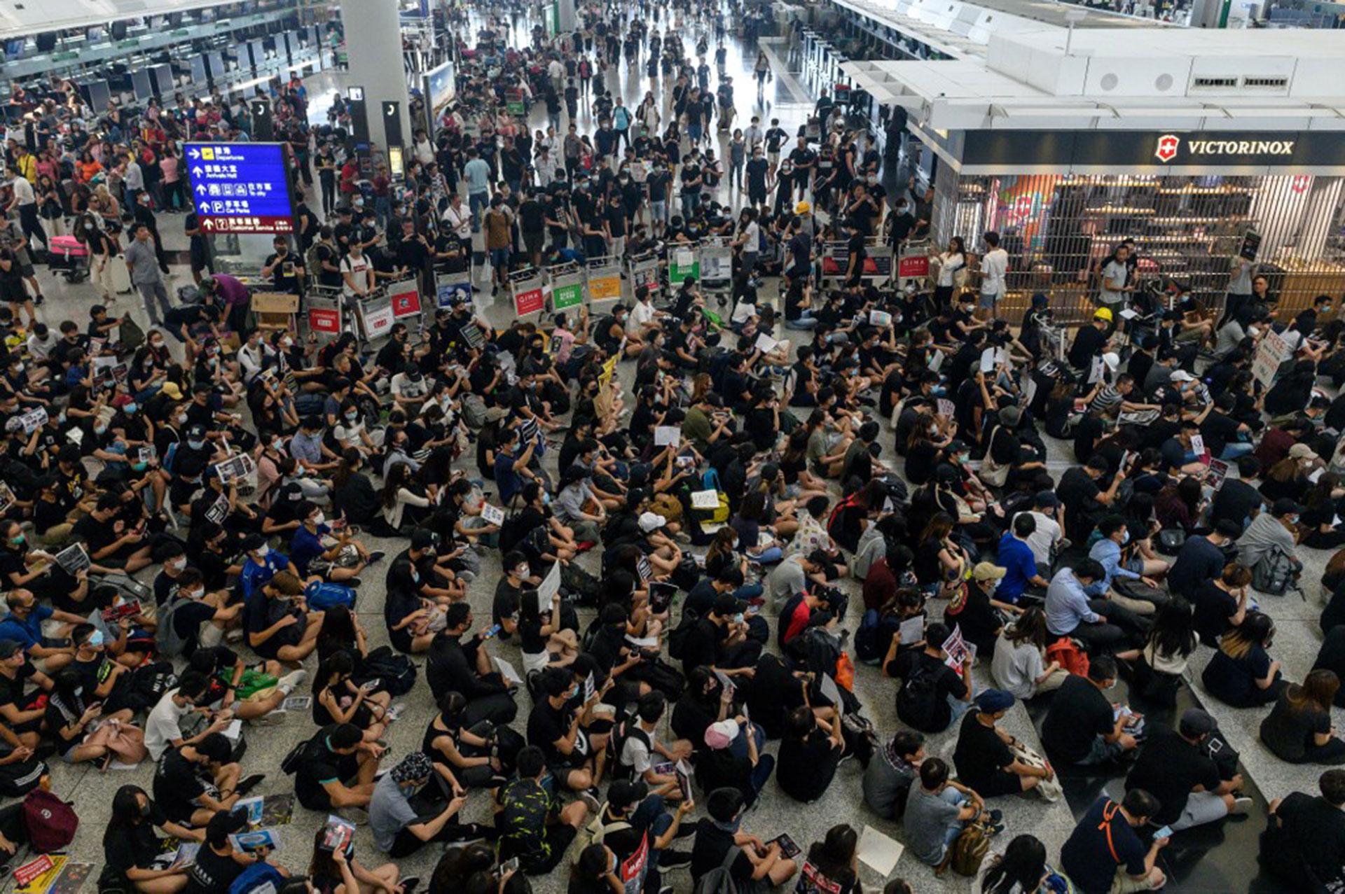 Manifestantes pro-democracia de Hong Kong bloquean el acceso a las puertas de salida durante otra manifestación en el aeropuerto internacional de Hong Kong el 13 de agosto de 2019 (Foto de Philip FONG / AFP)