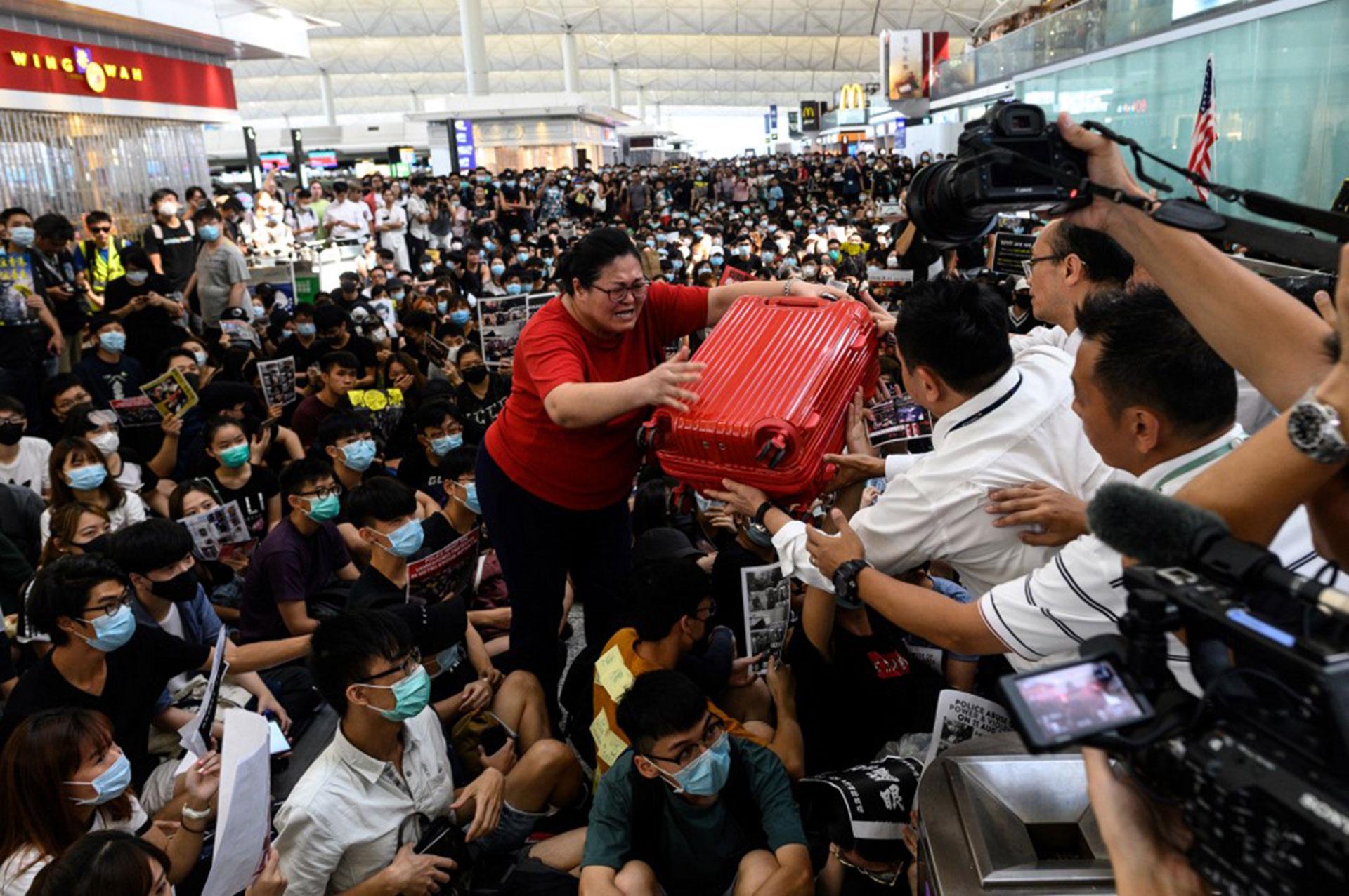 Una turista (C) entrega su equipaje a los guardias de seguridad cuando intenta entrar por la puerta de salida (Foto de Philip FONG / AFP)