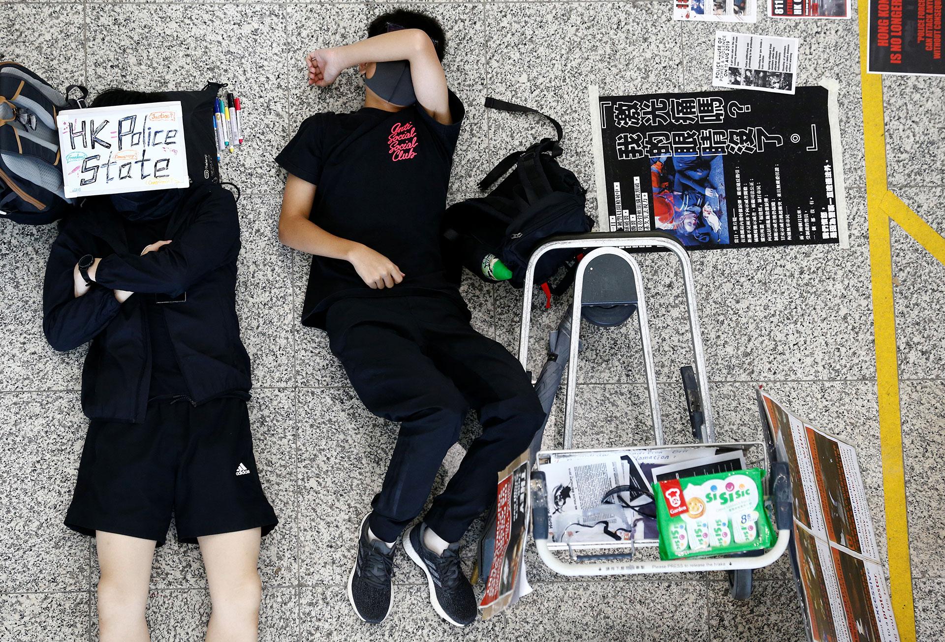 Dos jóvenes manifestantes antigubernamentales duermen en el suelo del aeropuerto de Hong Kong (REUTERS/Thomas Peter)