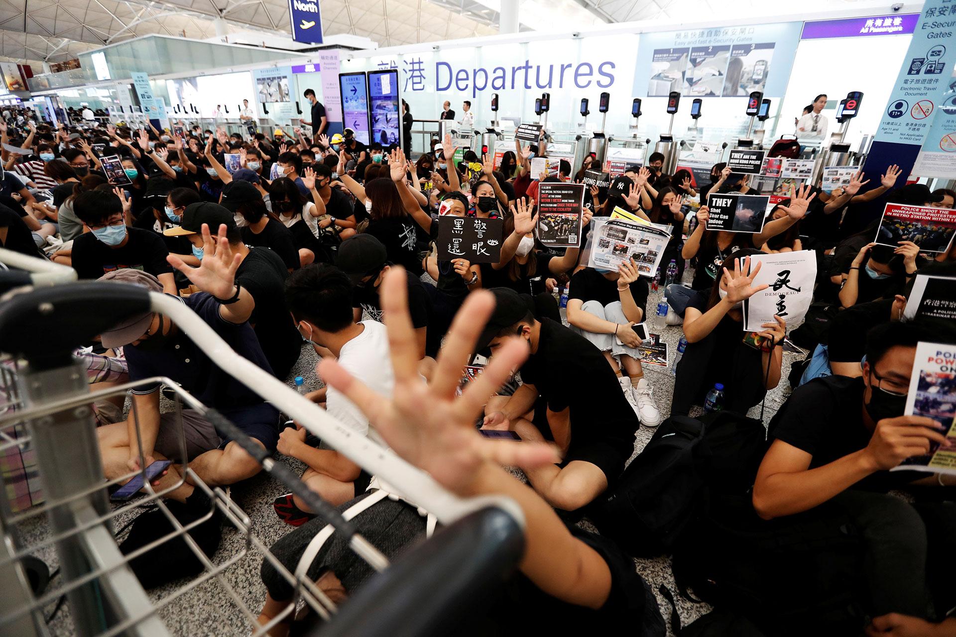 Los manifestantes antigubernamentales celebran después del anuncio de que todas las operaciones aeroportuarias fueron suspendidas debido a las protestas(REUTERS/Issei Kato).