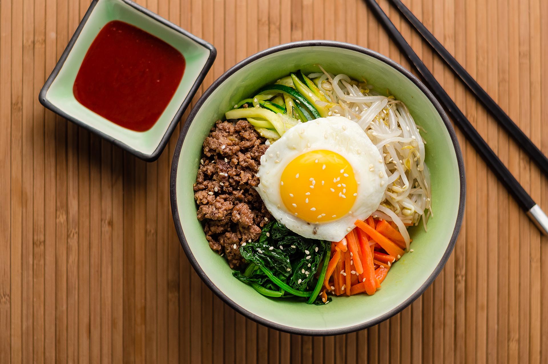 El bibimbap coreano es un colorido y sabroso bowl de arroz cubierto con un huevo frito y servidocon verduras calientes