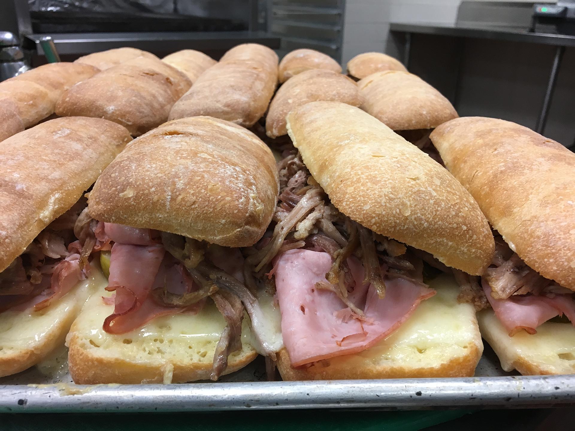 El simple pero delicioso sándwich cubano generalmente incluye jamón, queso suizo, cerdo, mostaza y encurtidos calentados entre dos crujientes panes
