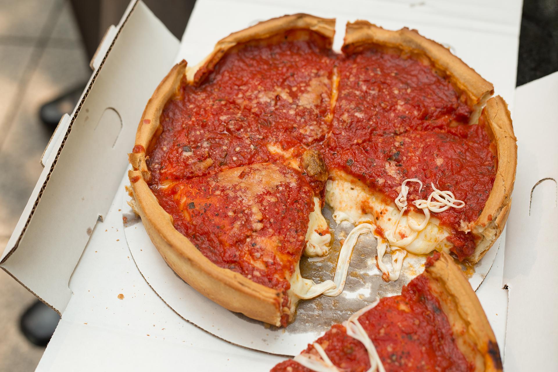La pizza estilo Chicago se elabora tradicionalmente abierta, como la focaccia, y tiene una base de pan gruesa, honda y crujiente, rellena de queso y salsa de tomate en trozos