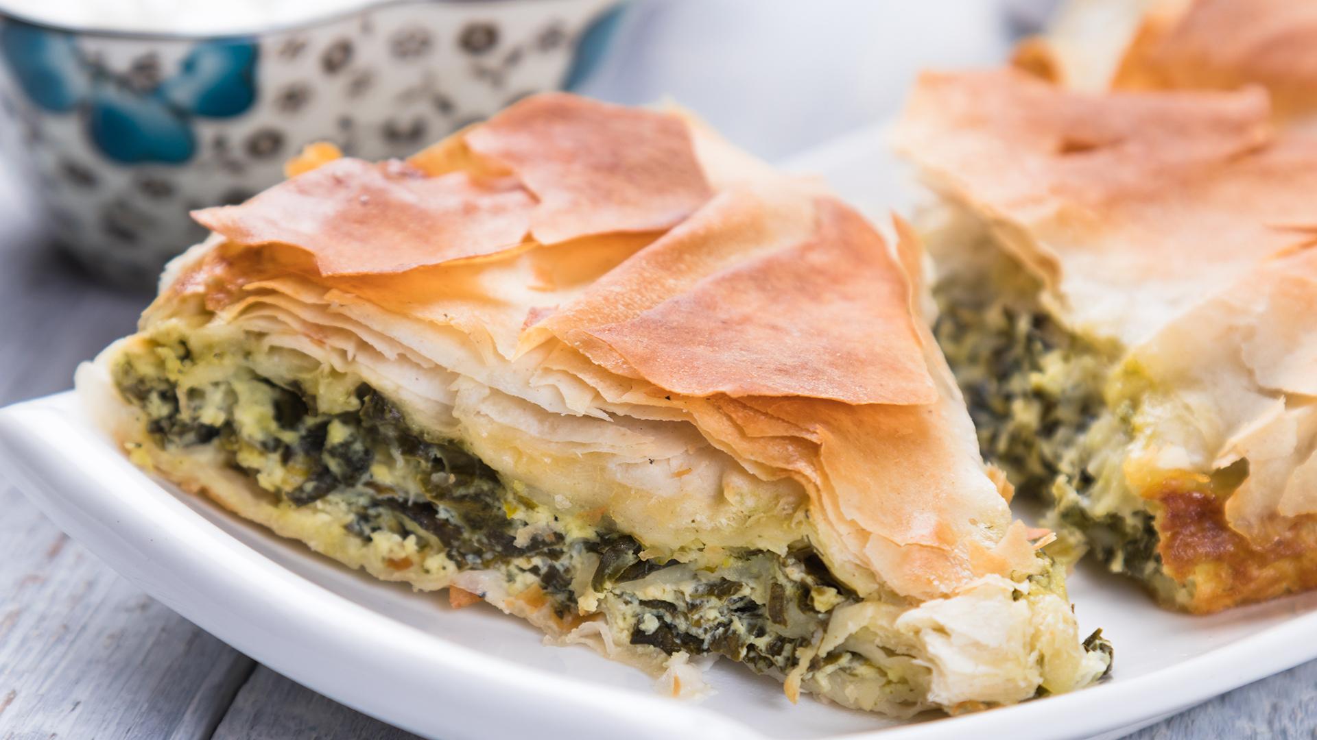 La spanakopita griega es un pastel hecho de masa filo escamosa, queso feta, espinacas, huevo y condimentos varios