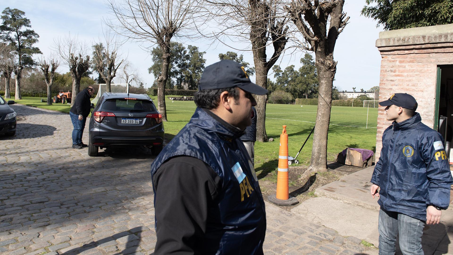 Seguridad de la Policía Federal en Los Abrojos. En el fondo, el automóvil del presidente del Banco Central, Guido Sandleris
