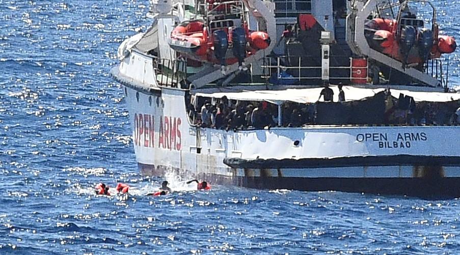 Migrantes nadan después de saltar del barco de rescate español Open Arms, cerca de la costa italiana en Lampedusa, Italia, el 20 de agostoa la mañana (REUTERS/Guglielmo Mangiapane)