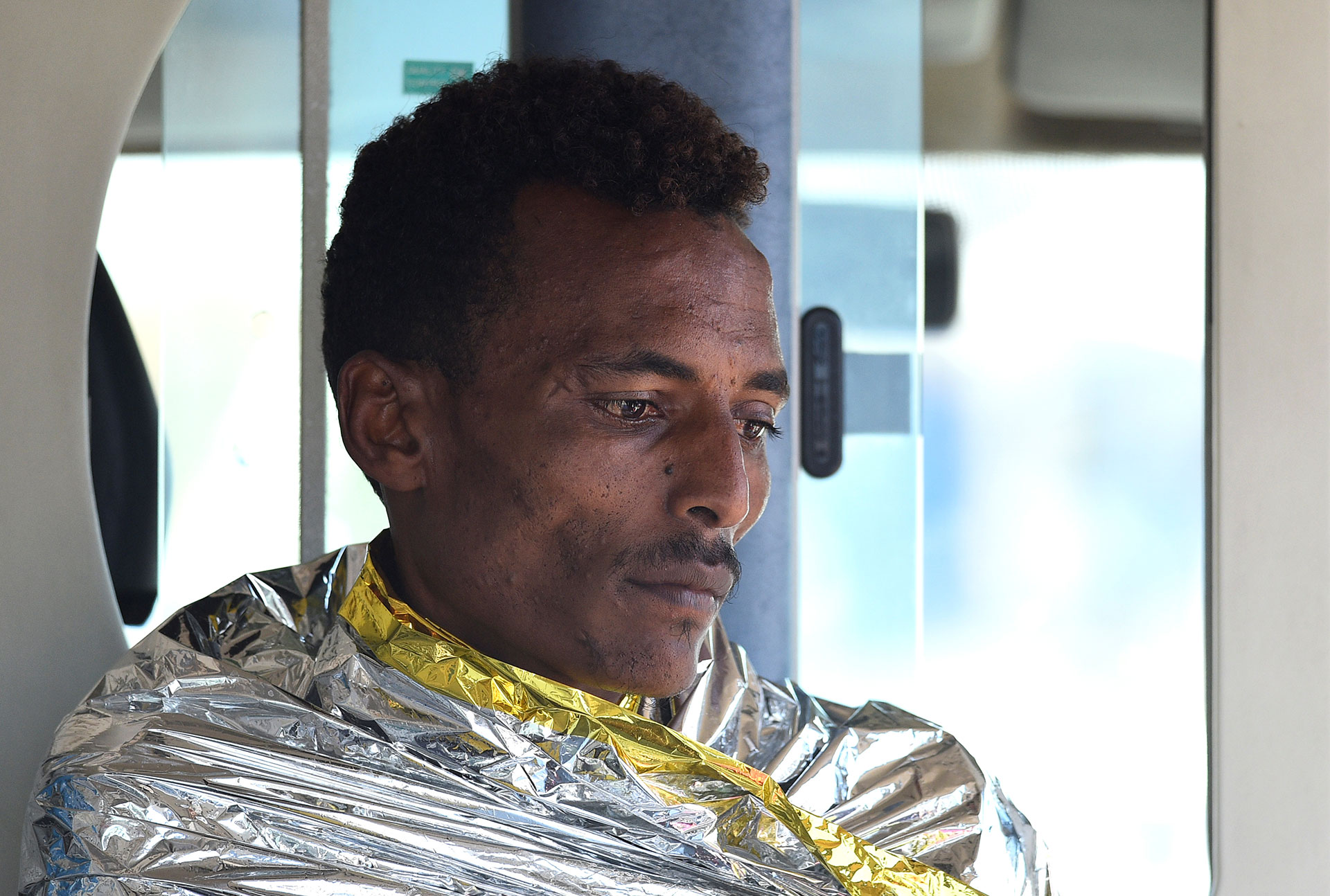 Otro de los hombresque saltaron del Open Arms es trasladado en una ambulancia en Lampedusa (REUTERS/Guglielmo Mangiapane)