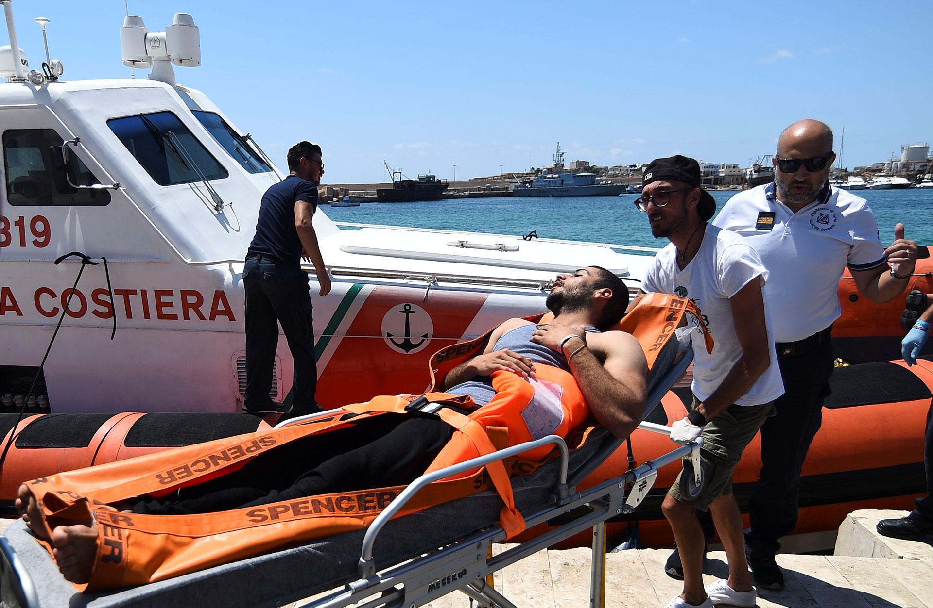 Un migrante que saltó del barco de rescate español es llevado en una camilla, en Lampedusa, Italia (REUTERS/Guglielmo Mangiapane).