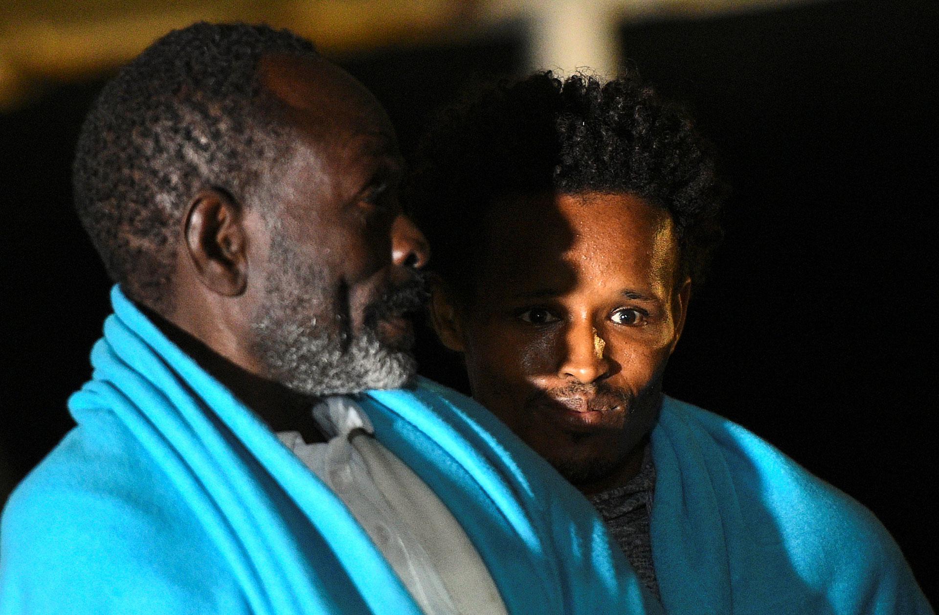 Dos hombres observan el muelle tras el arribo del barco(REUTERS/Guglielmo Mangiapane)