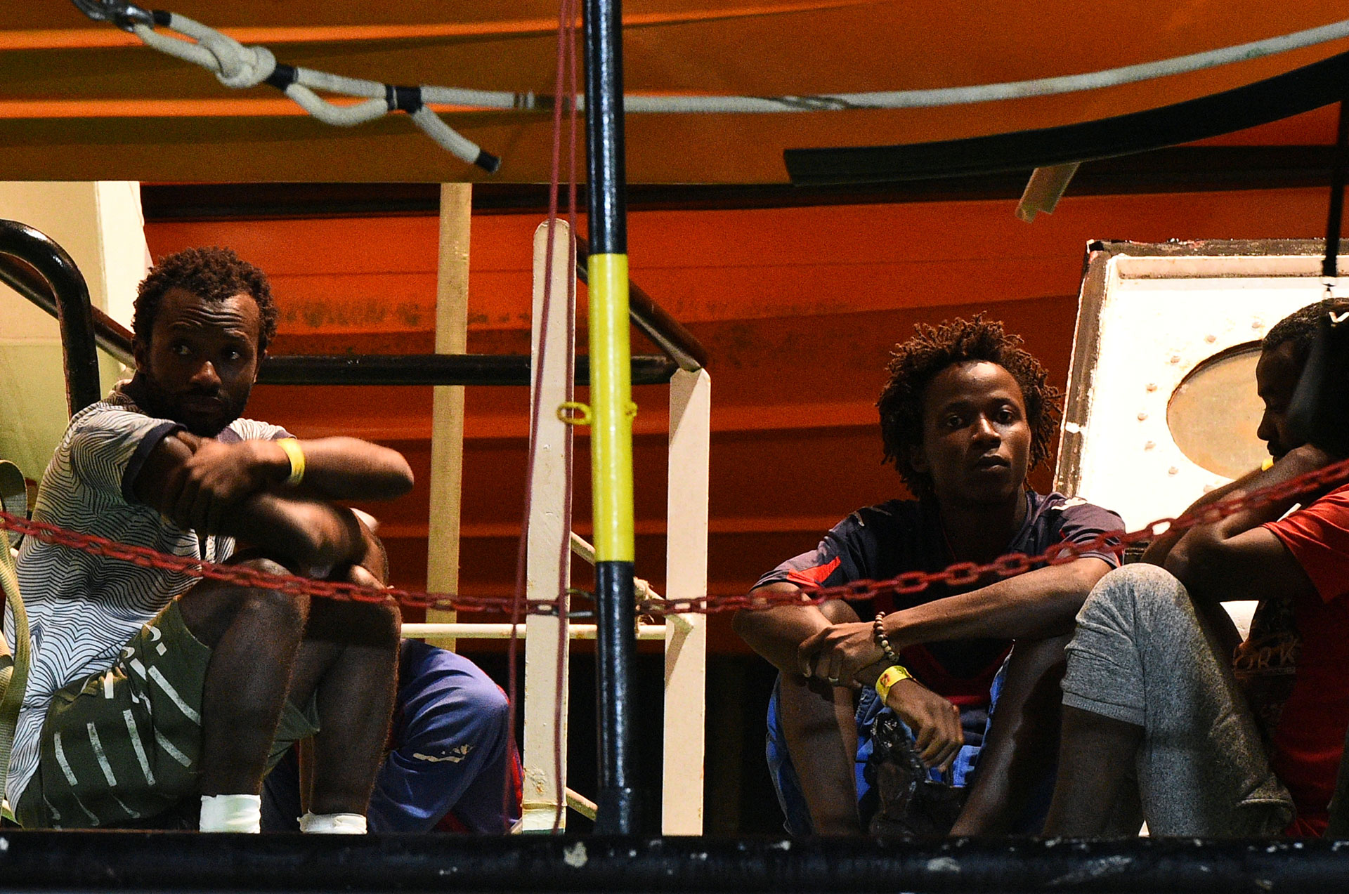 Migrantes miran desde el barco de rescate español Open Arms NGO, tras la llegada a Lampedusa (REUTERS/Guglielmo Mangiapane)