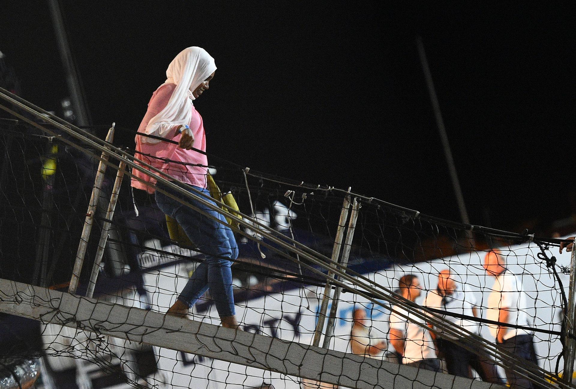 Una migrante desembarca del Open Arms el 20 de agostoa la noche (REUTERS/Guglielmo Mangiapane)
