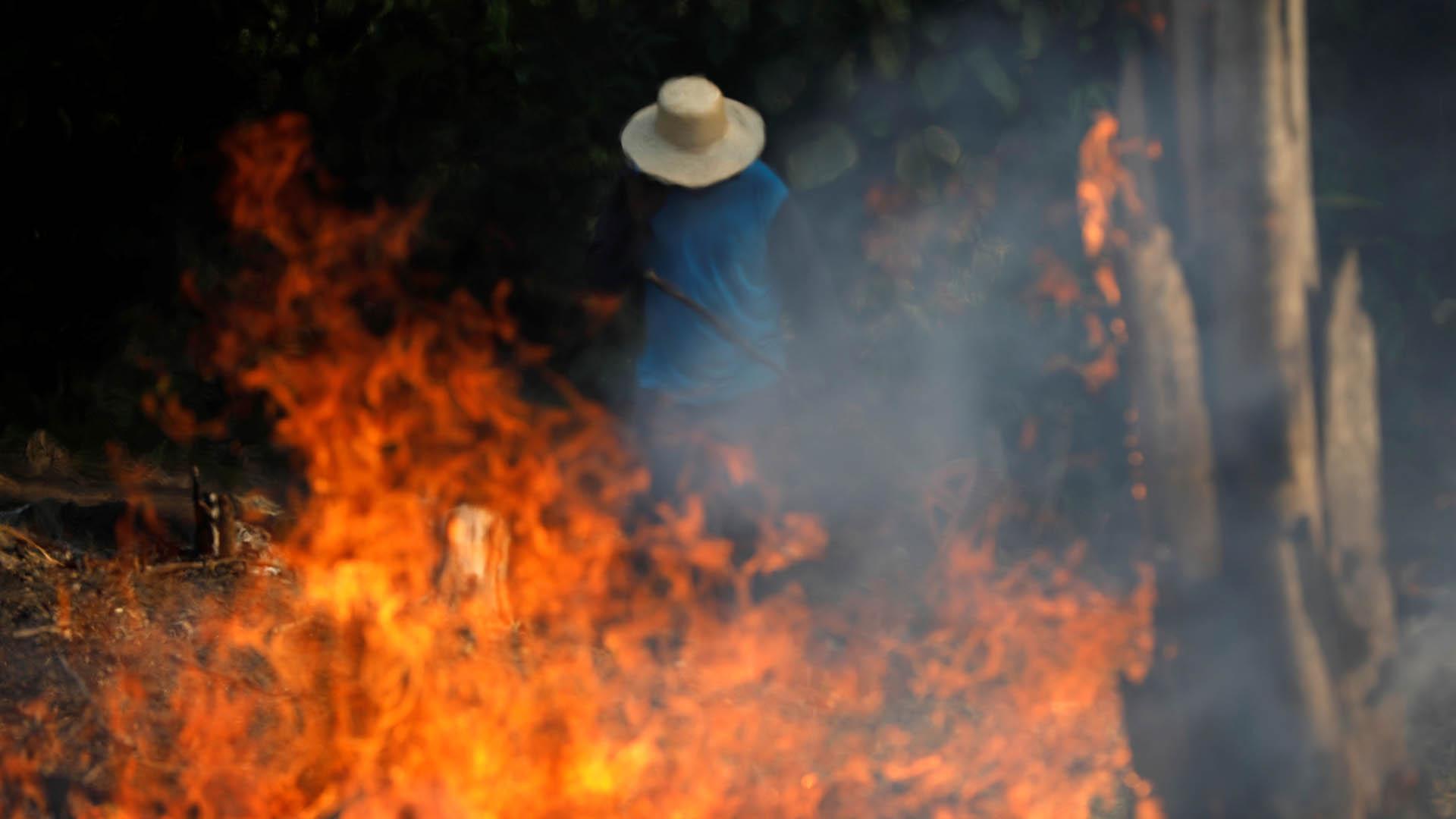 Un hombre trabaja para apagar el fuego (REUTERS/Bruno Kelly)