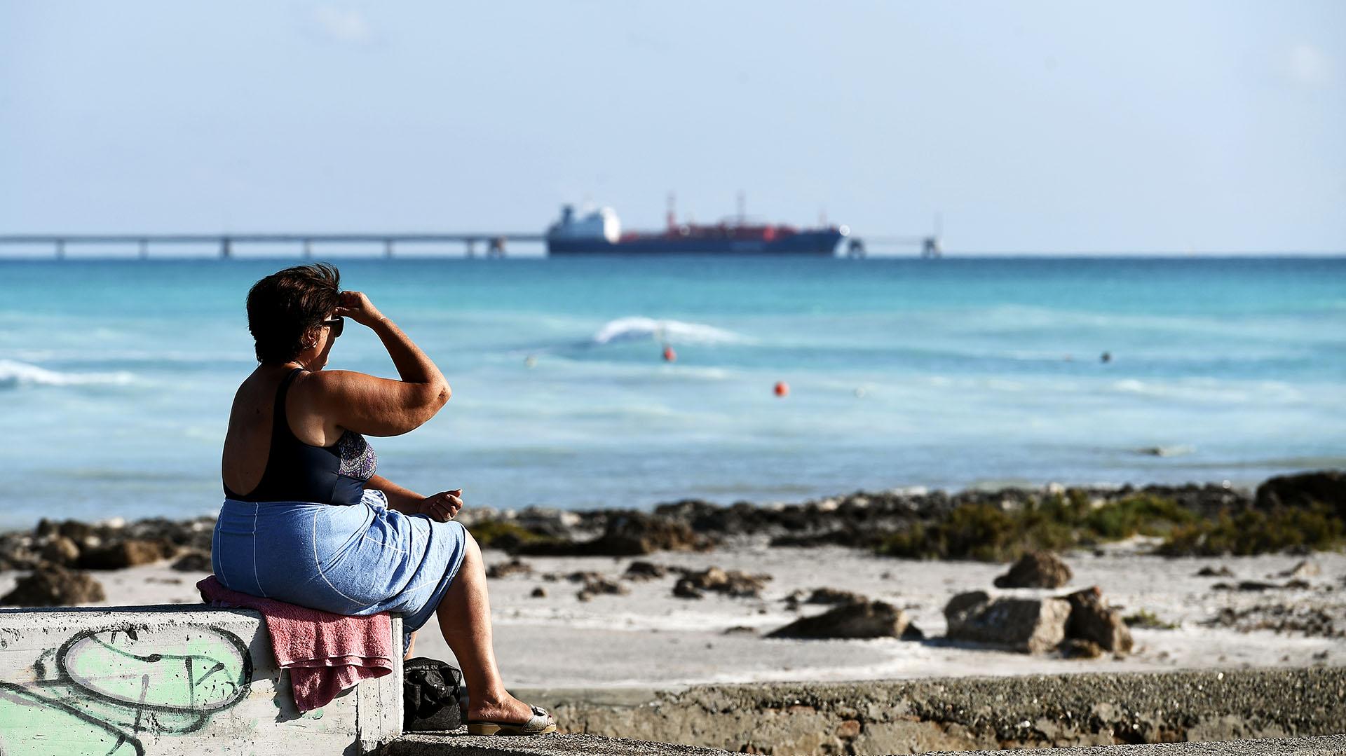 """Una mujer mira en la playa """"Spiagge Bianche"""" (arena blanca), mientras un barco pasa. (Foto de Vincenzo PINTO / AFP)"""
