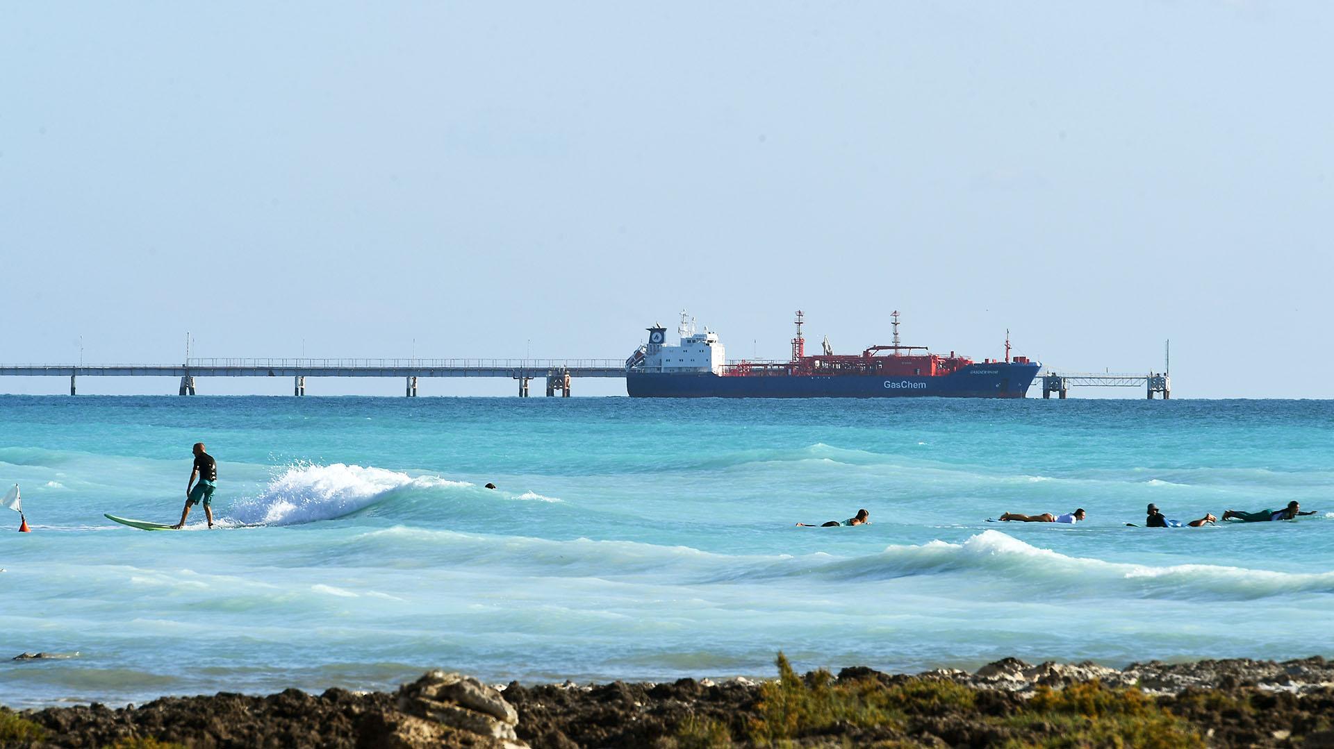 """Un hombre surfea mientras un barco navega junto a la playa """"Spiagge Bianche"""" (arena blanca), Foto de Vincenzo PINTO / AFP)"""