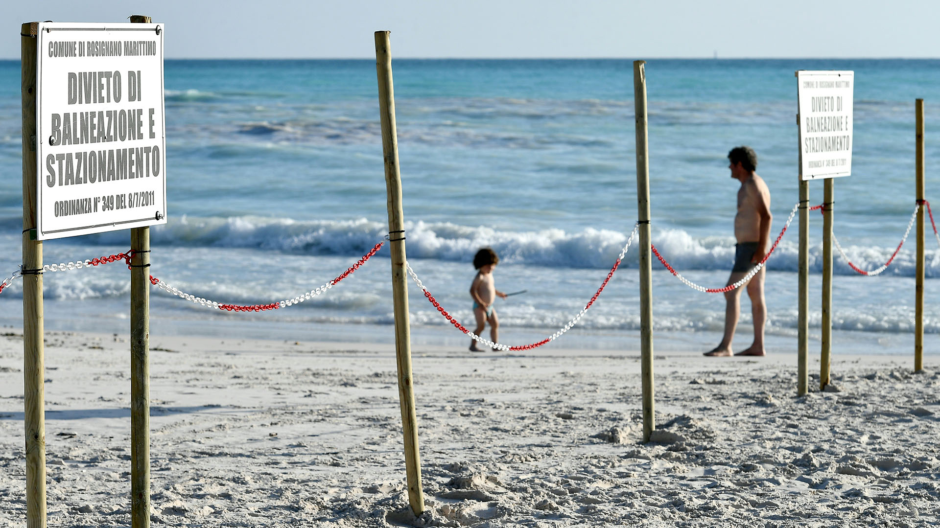 """Un hombre y un niño caminan detrás de un cartel que dice """"prohibido bañarse y estacionarse"""" en la playa """"Spiagge Bianche"""" (arena blanca) en Rosignano Solvay (Foto de Vincenzo PINTO / AFP)"""