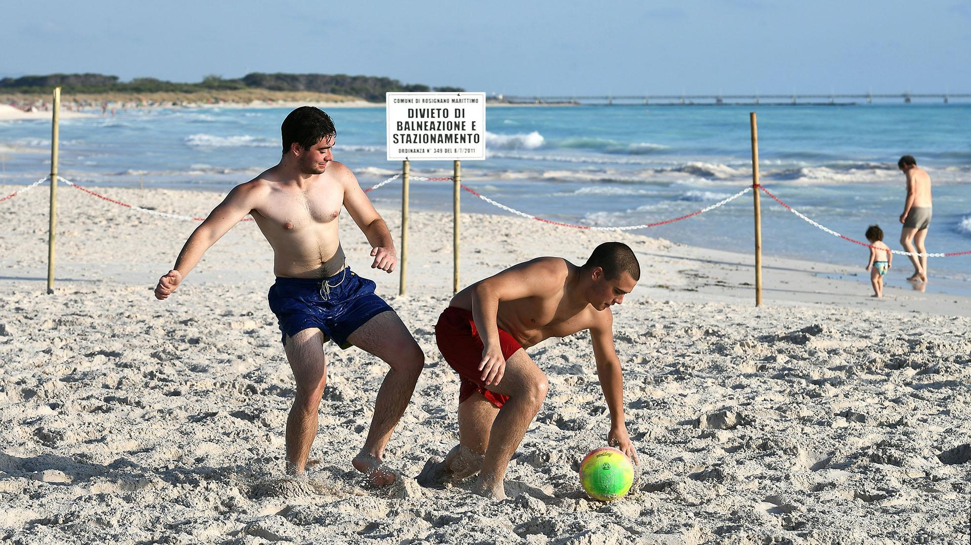 """Dos hombres juegan con una pelota frente a un letrero que dice """"prohibido bañarse y estacionarse"""" en la playa. (Foto de Vincenzo PINTO / AFP)"""