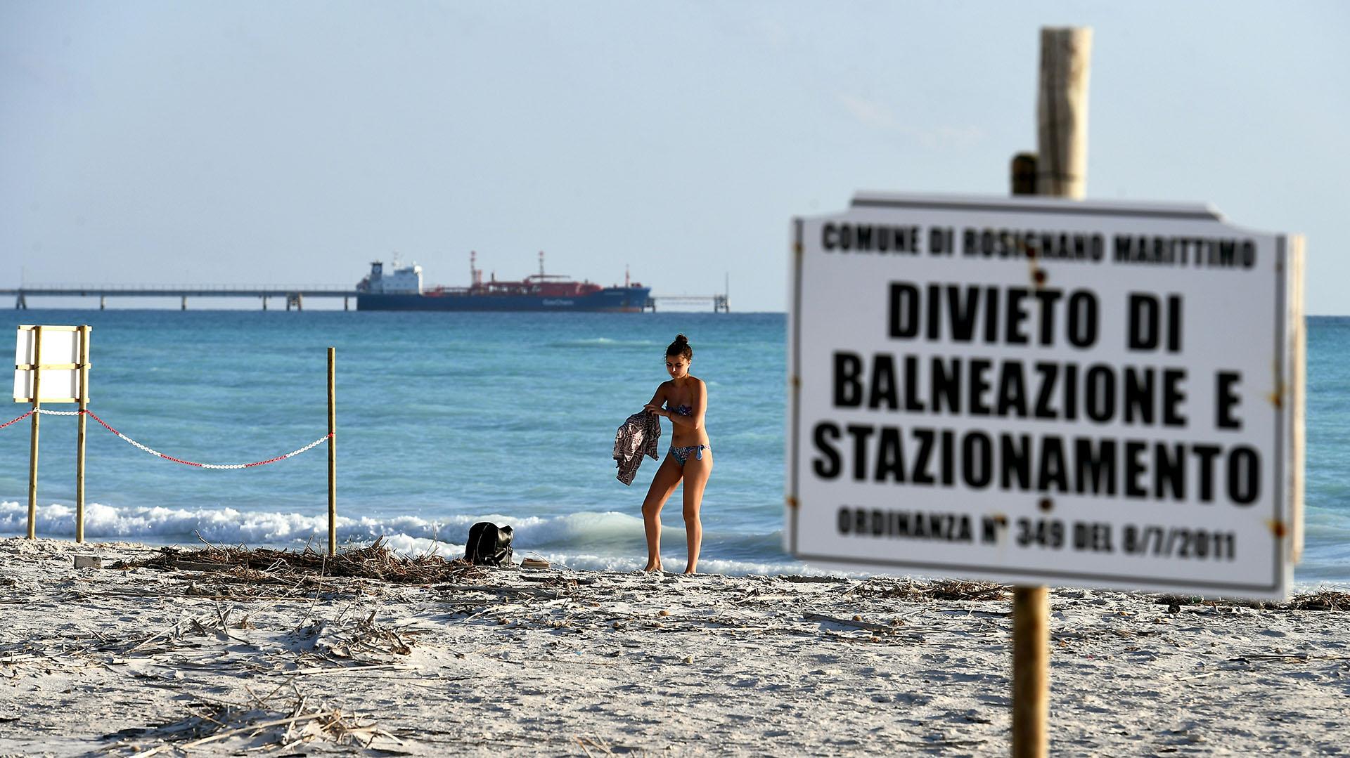 """Una mujer se viste detrás de un cartel que dice """"prohibido bañarse y estacionarse"""" (Foto de Vincenzo PINTO / AFP)"""