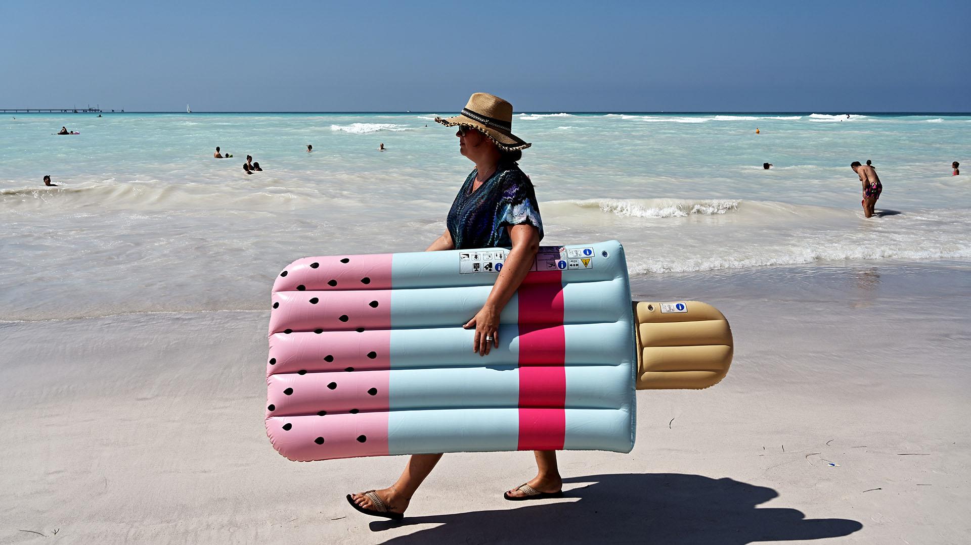 Una mujer sostiene un colchón inflable de helado mientras camina por la playa. (Foto de Vincenzo PINTO / AFP)