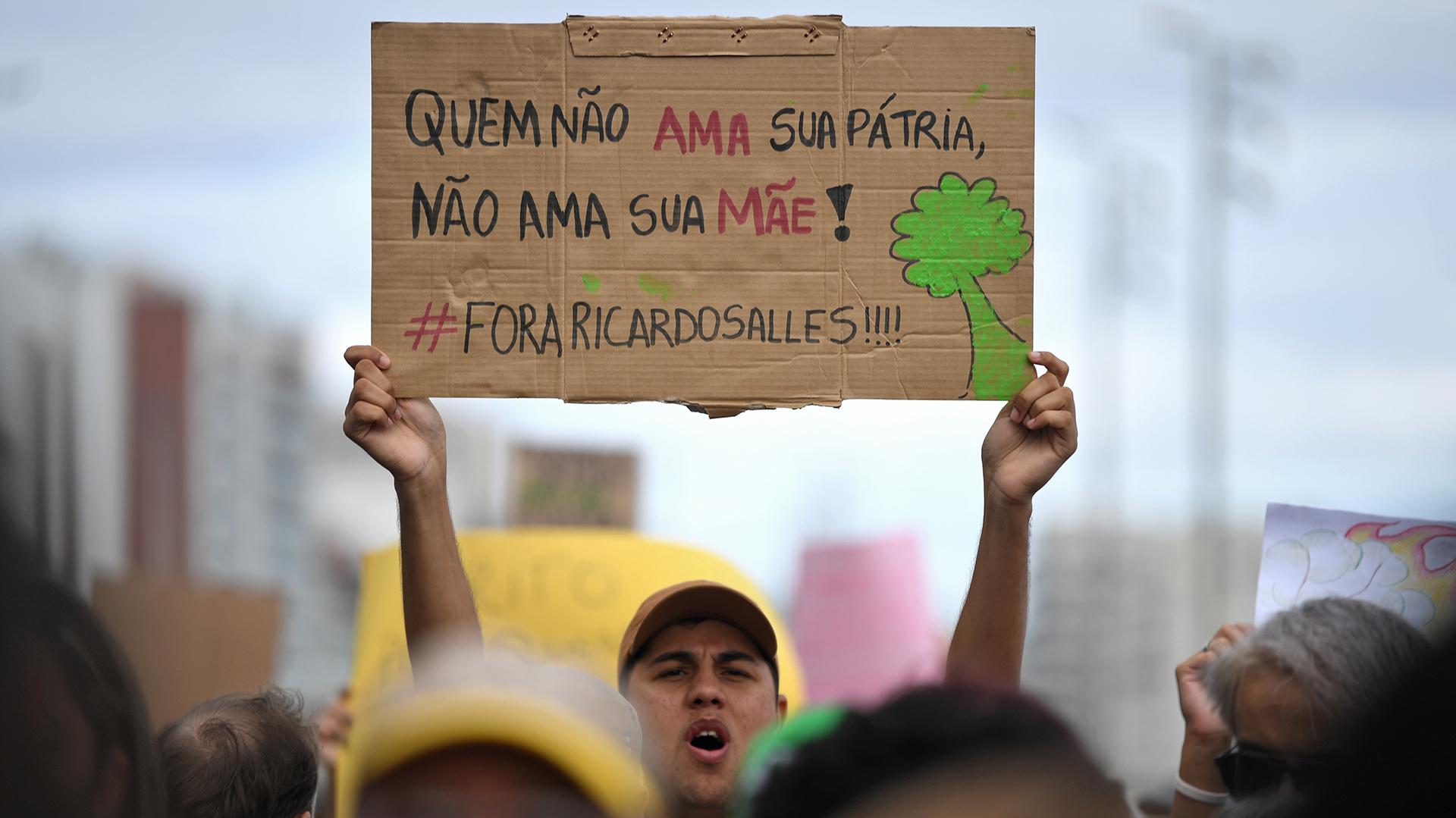 """Un activista sostiene un cartel que dice """"Aquel que no ama a su patria, no ama a su madre"""" durante la protesta. (Foto por Mauro PIMENTEL / AFP)"""