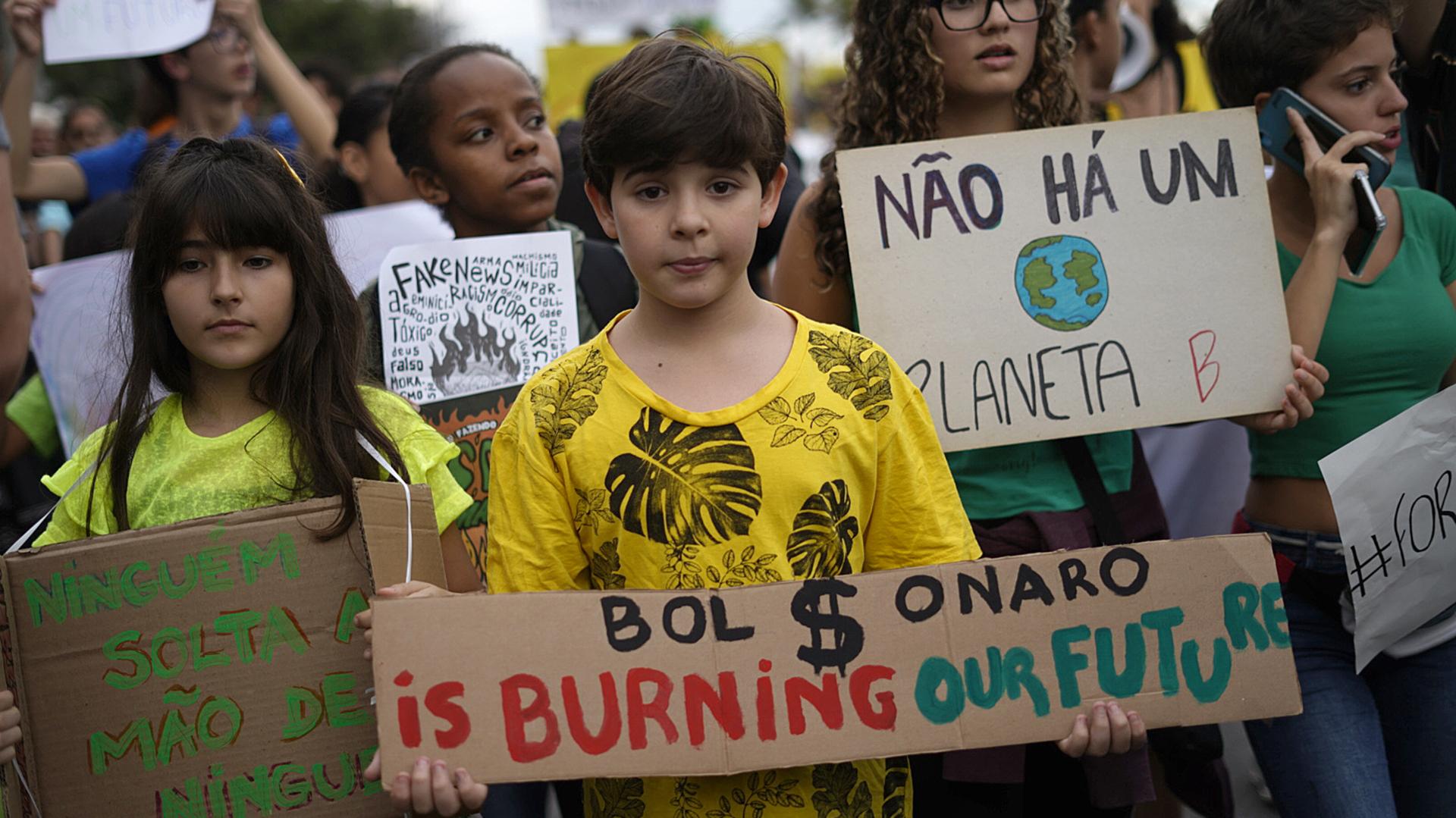 """Un niño sostiene un cartel que dice """"Boslonaro esta quemando nuestro futuro"""". (Foto por Mauro PIMENTEL / AFP)"""