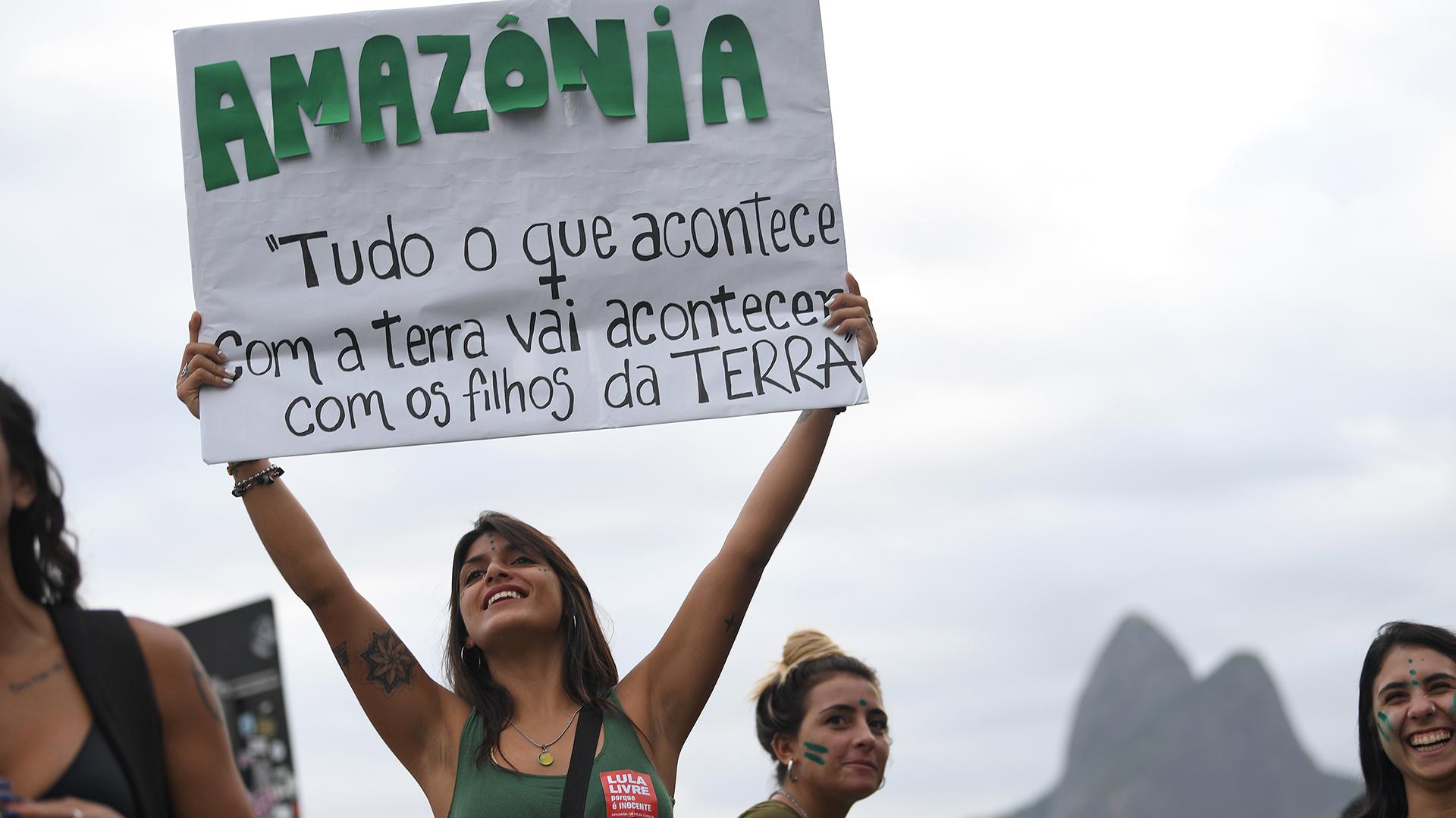 """Un activista sostiene un cartel que dice """"Todo lo que sucede en la Tierra, les pasará a los niños de la Tierra"""" durante la protesta. (Foto por Mauro PIMENTEL / AFP)"""